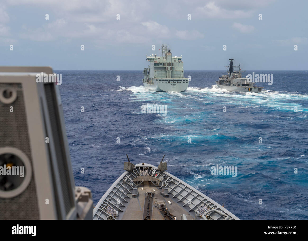 180711-N-YR245-0518 PACIFIC OCEAN (July 11, 2018) Ticonderoga-class guided-missile cruiser USS Lake Champlain (CG 57) approaches Royal Canadian Navy replenishment vessel MV Asterix with Chilean frigate CNS Almirante Lynch (FF 07) alongside at a replenishment-at-sea approach training during Rim of the Pacific (RIMPAC) exercise, July 11. Twenty-five nations, 46 ships and five submarines, and about 200 aircraft and 25,000 personnel are participating RIMPAC from June 27 to Aug. 2 in and around the Hawaiian Islands and Southern California. The world's largest international maritime exercise, RIMPAC Stock Photo