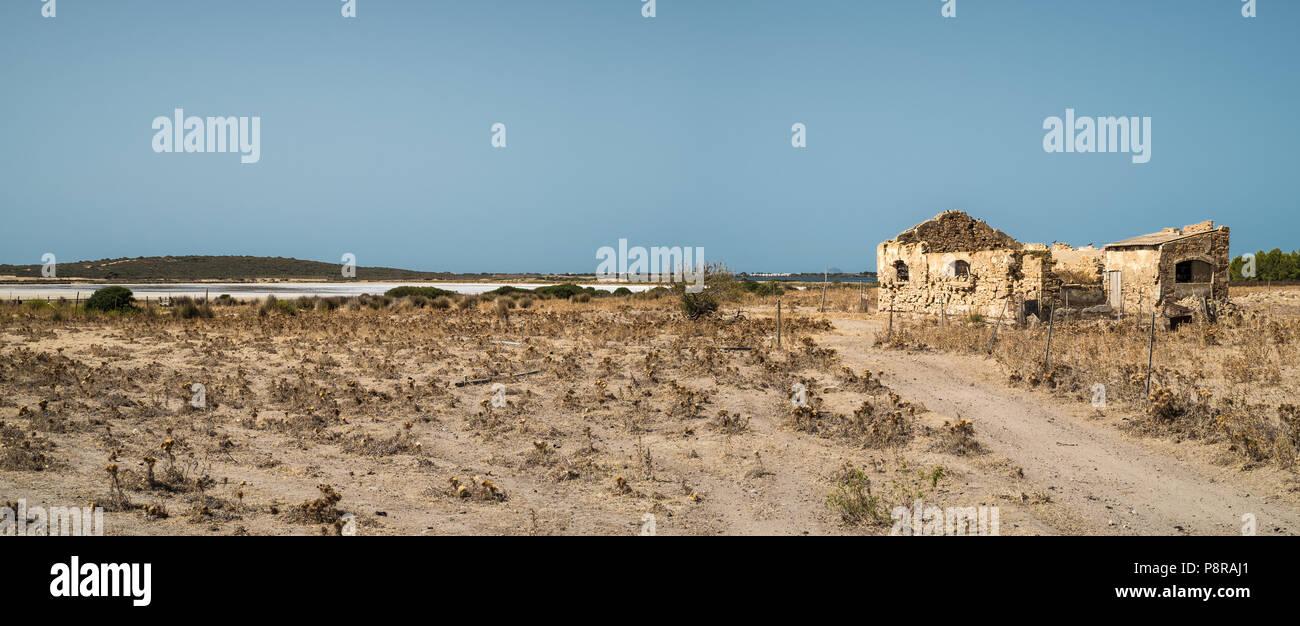 Abandoned ruins of a house in a arid land. Sant'Anna Arresi, Carbonia Iglesias, Sardinia, Italy. - Stock Image