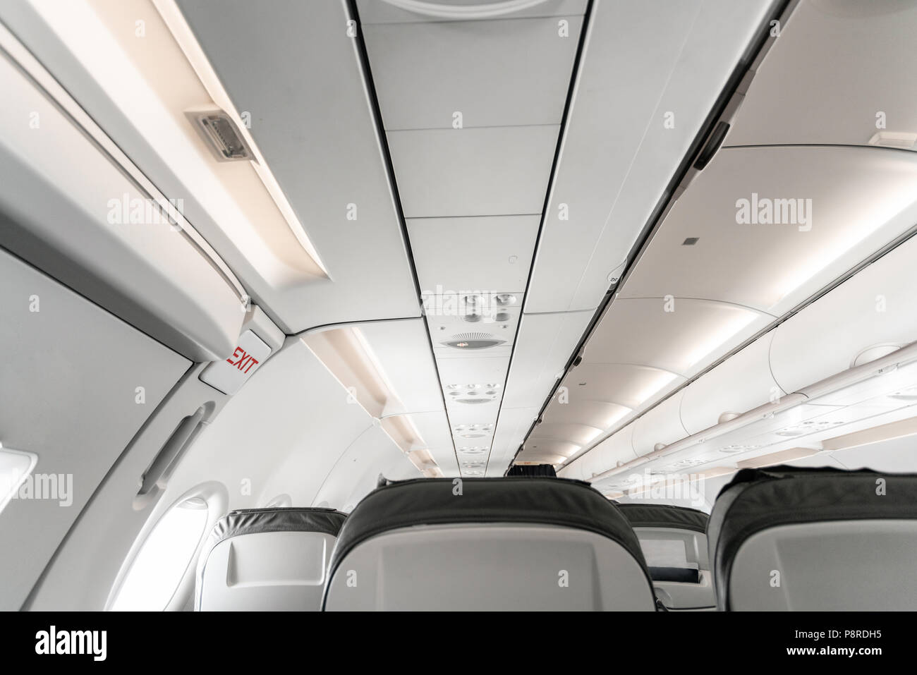 Emergency exit on an aircraft, view from inside of the plane. Empty airplane seats in the cabin. Modern Transportation concept. Aircraft long-distance international flight - Stock Image