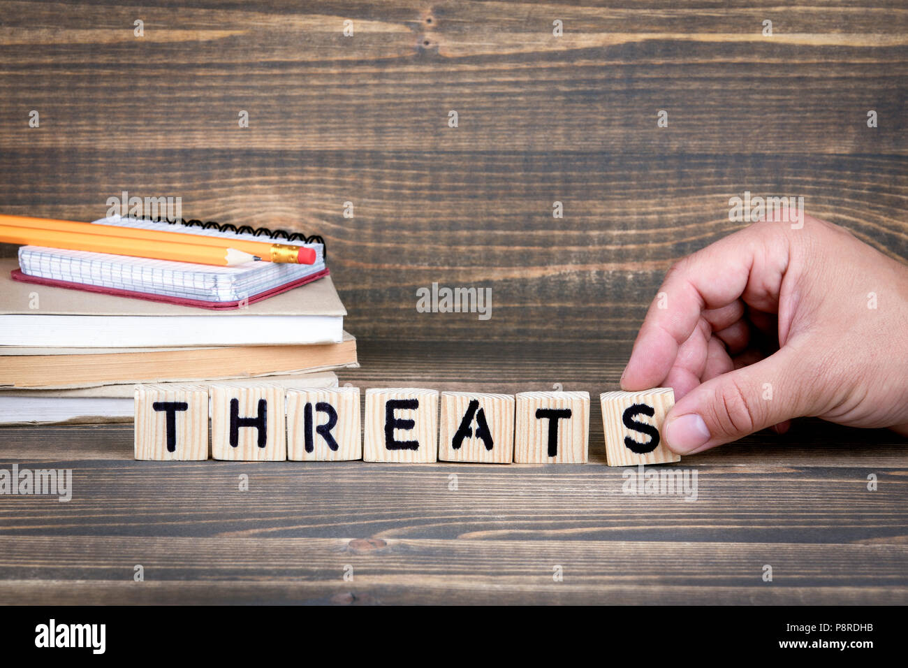 Threats. Wooden letters on the office desk, informative and communication background - Stock Image