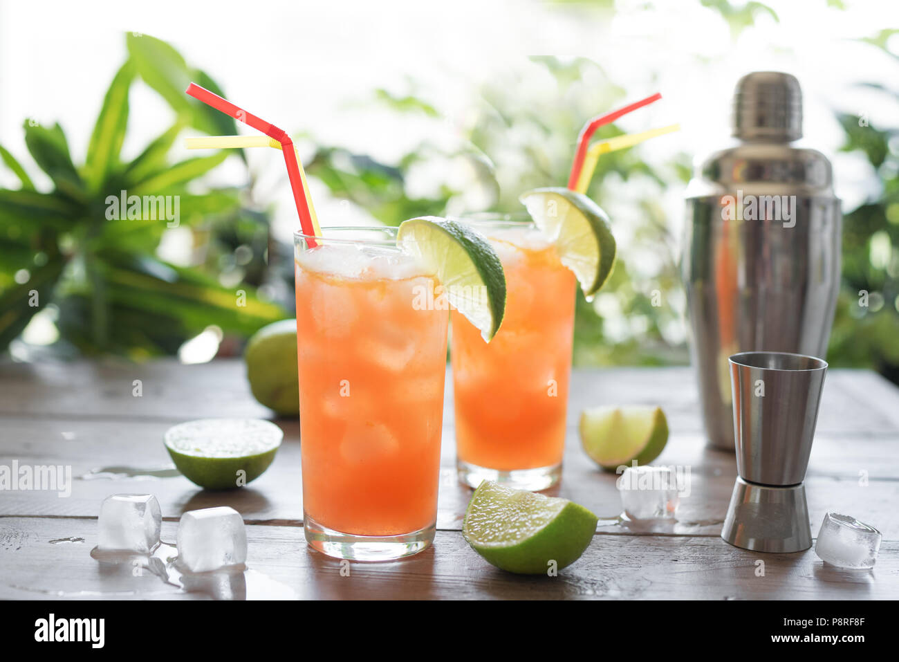 Zombie Cocktail with Rum, garnished with lime. Cold sweet summer fruit red alcohol cocktail, refreshing drink on wooden table, copy space. - Stock Image