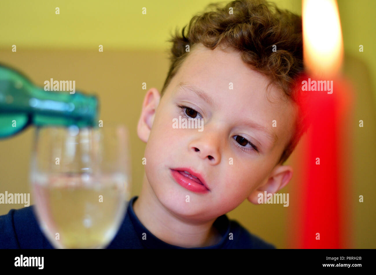 A small child in the restaurant serves himself - Stock Image