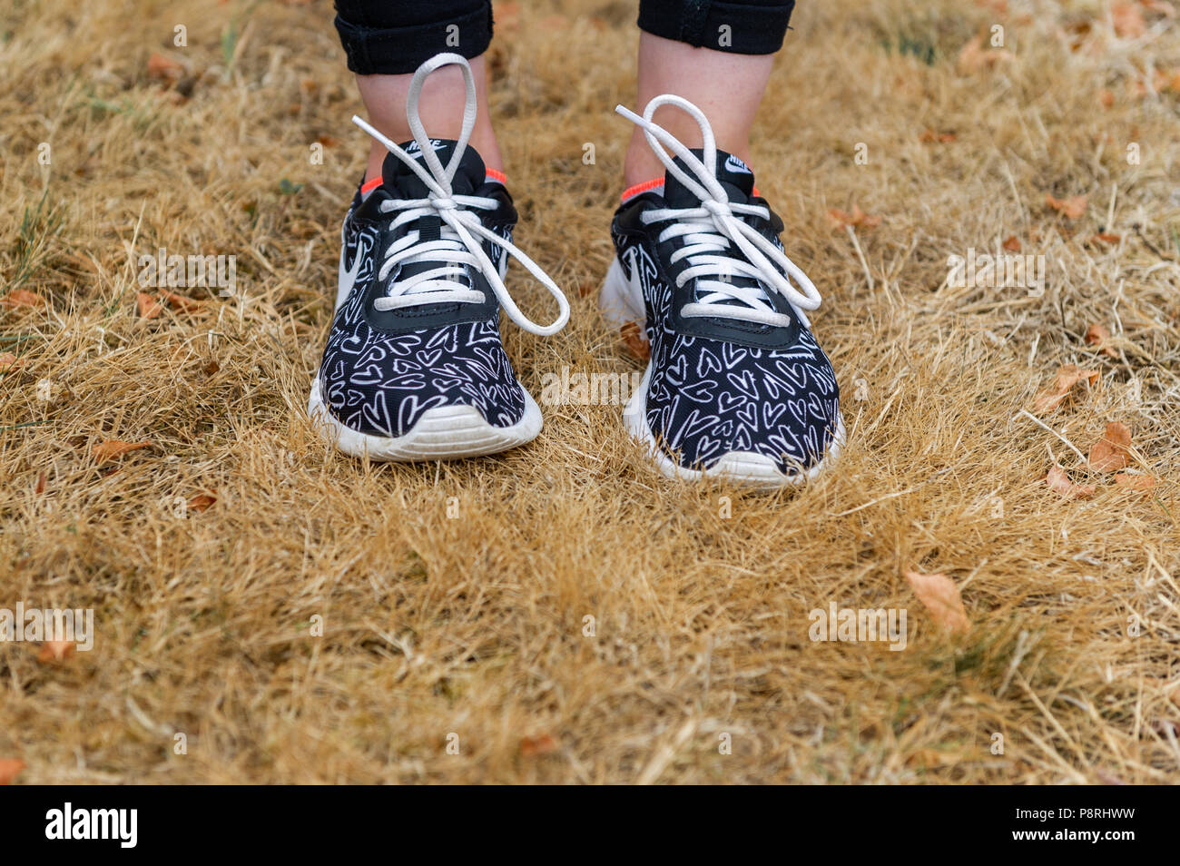 Dead grass due to the heatwave/drought with a young girl standing on it wearing training shoes in West Cork, Ireland. - Stock Image