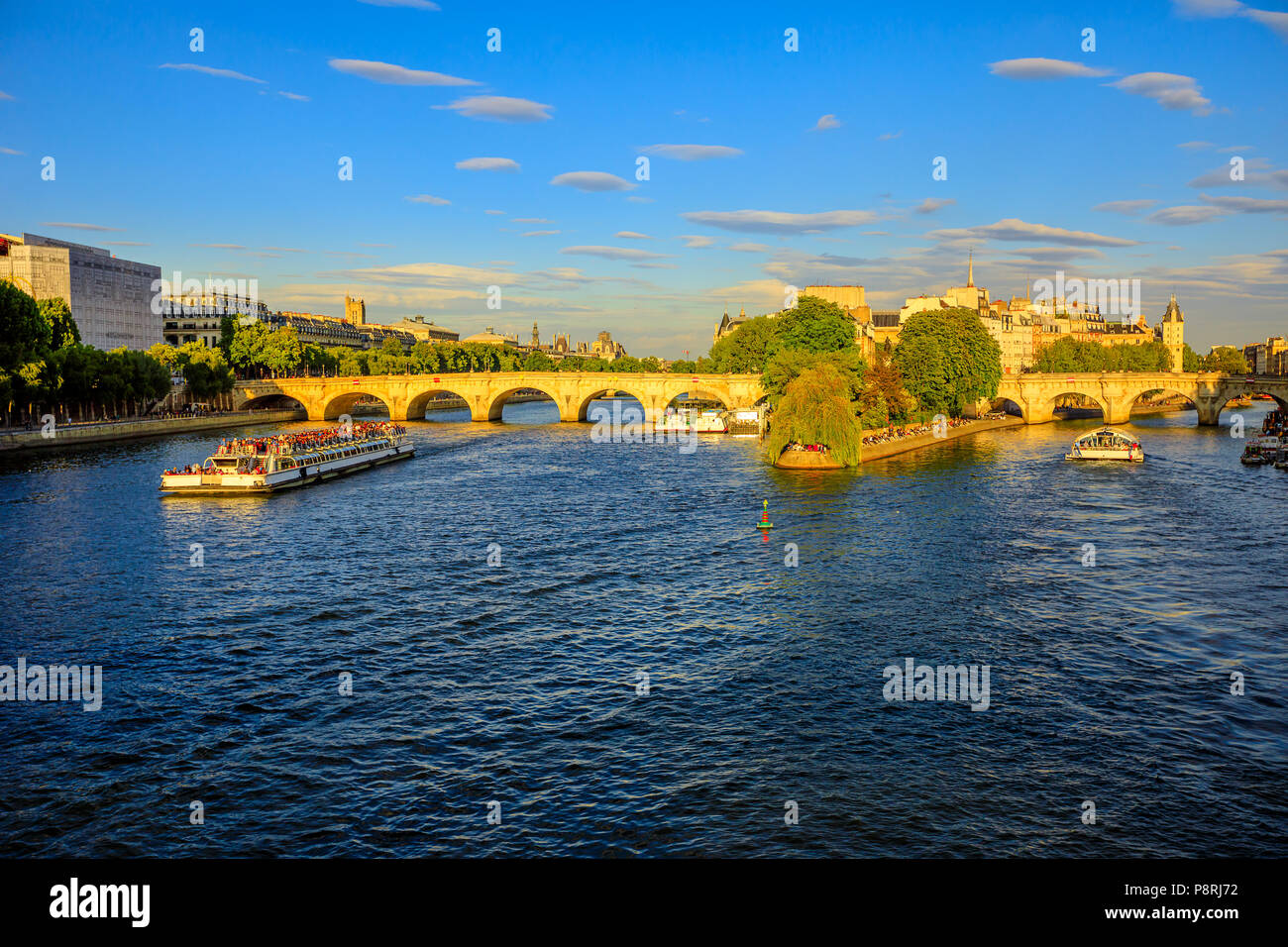 Tourist cruise on Seine river. Bateau mouche from Pont Neuf bridge and Notre Dame church on background. Tourist travelers in popular landmarks of Paris in France at sunset from Pont des Arts bridge. - Stock Image