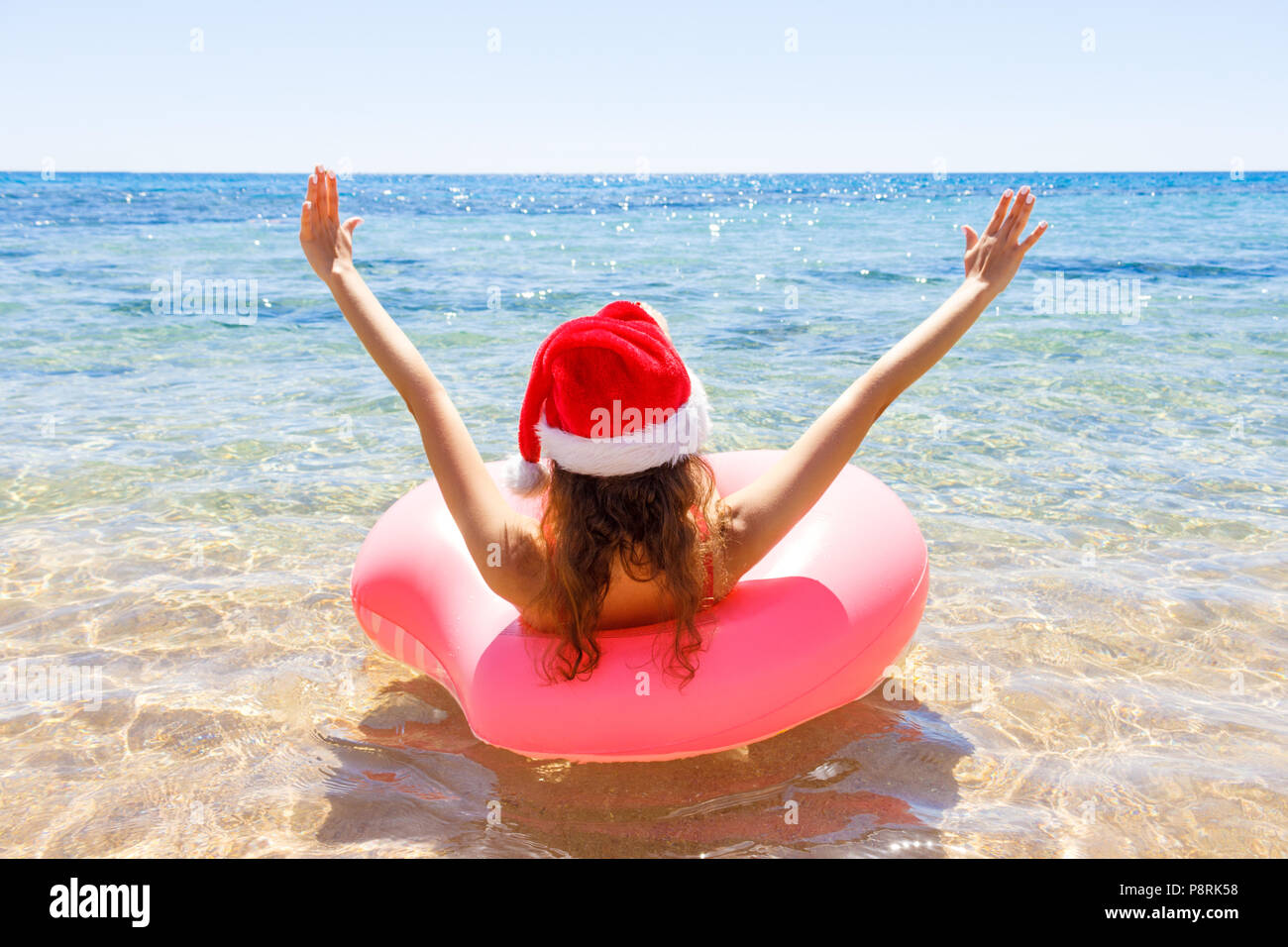 bd76f2379 Crazy swimming with inflatable donut and christmas hat on the beach ...