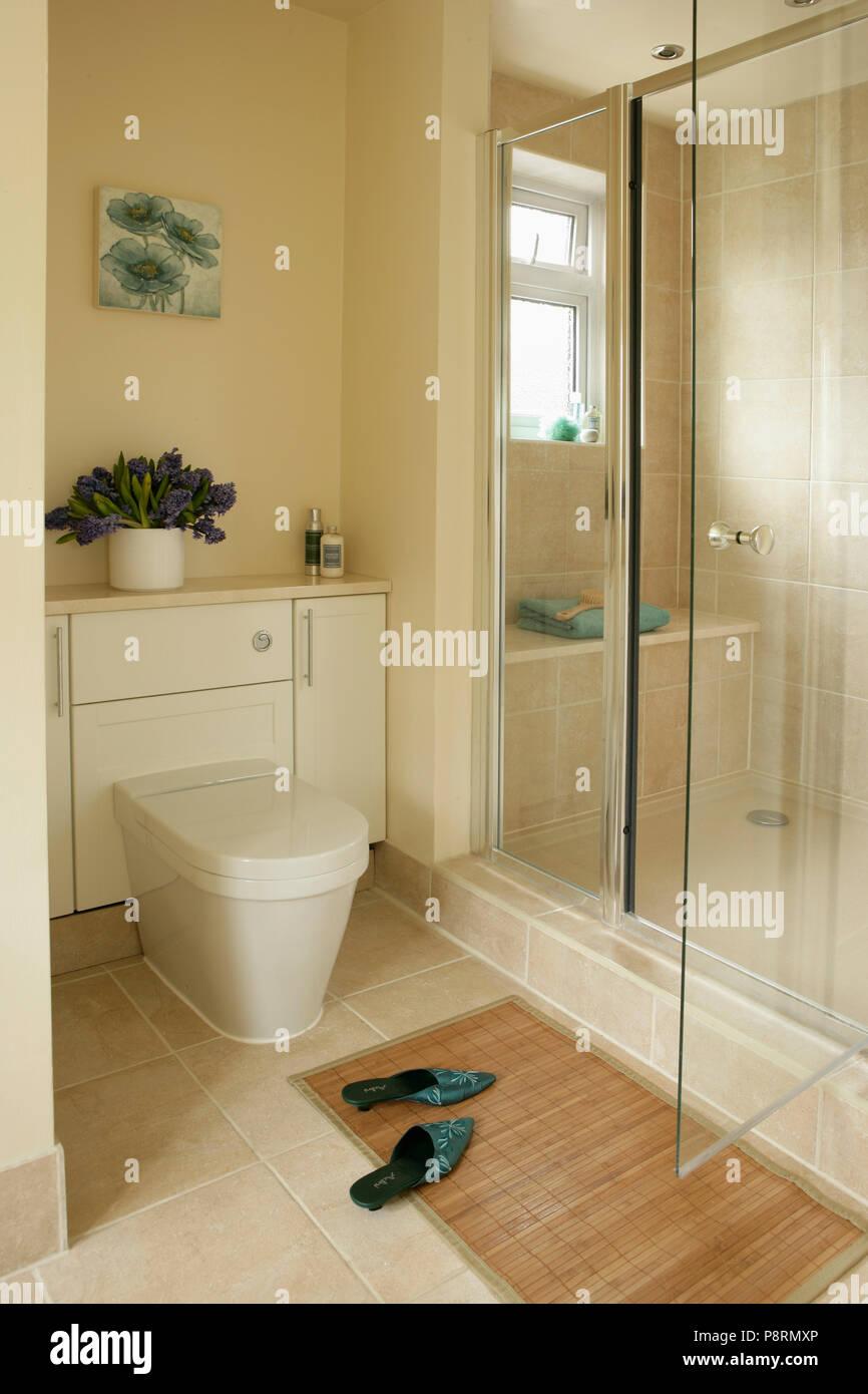 Toilet Beside Large Walk In Shower With Glass Doors In Modern Cream Bathroom