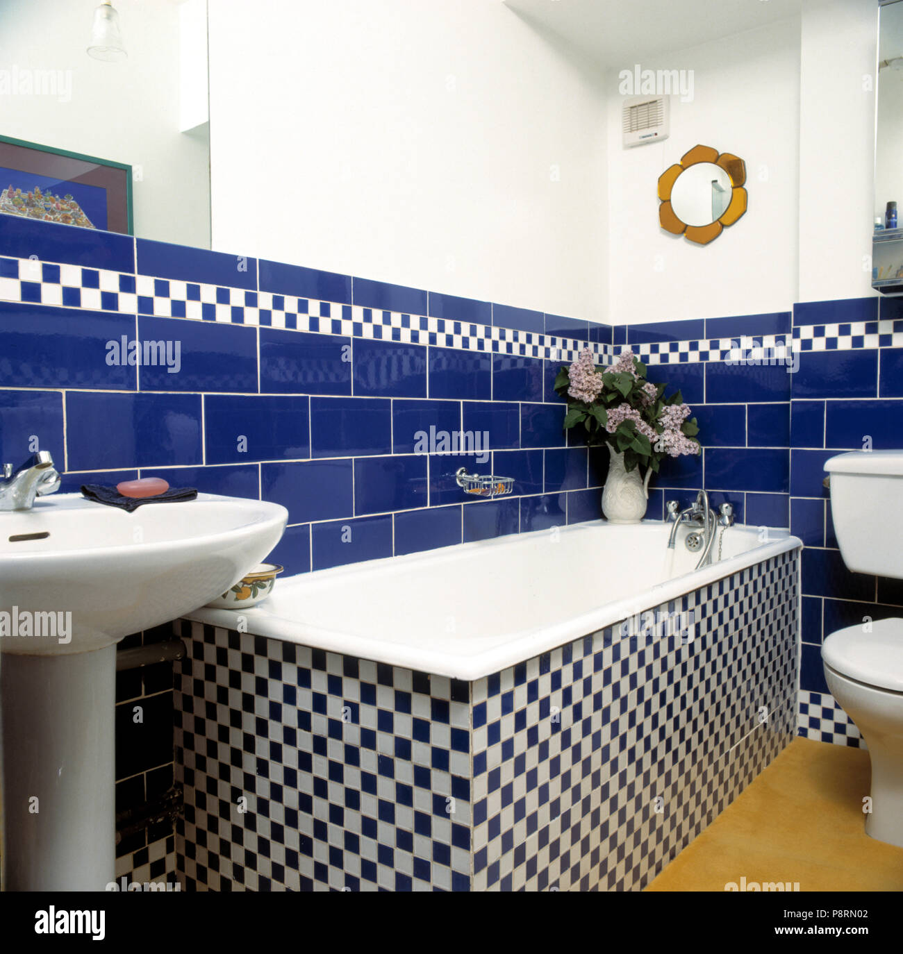 Blue ceramic tiles above bath with black+white chequerboard surround in white traditional bathroom - Stock Image