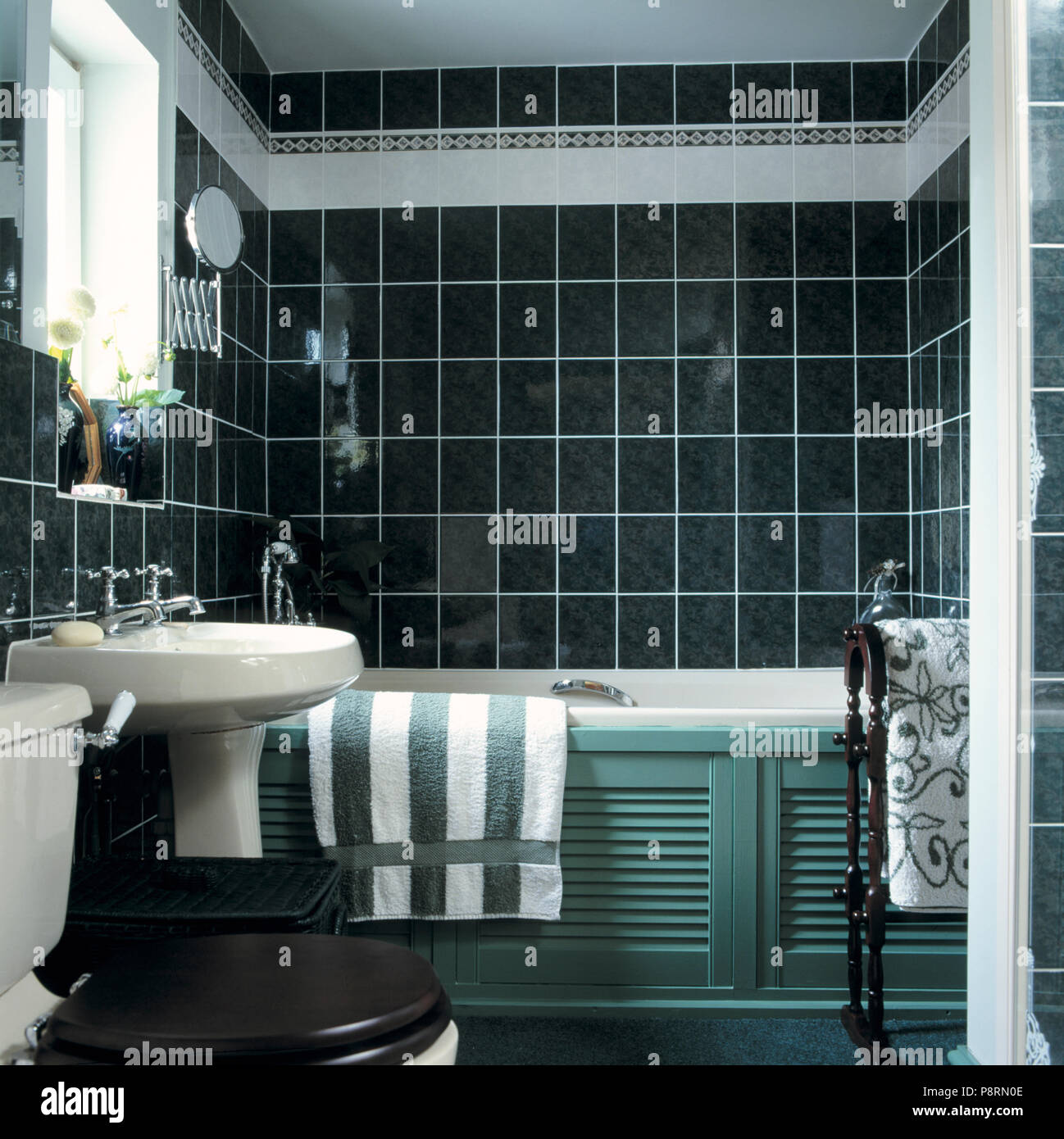 Green+white Striped Towel On Bath With Louvre Panelling In Black Tiled  Bathroom