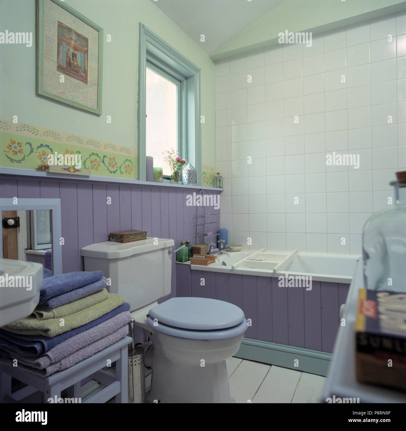 Pile Of Mauve Towels Beside Toilet With Mauve Seat In Bathroom With