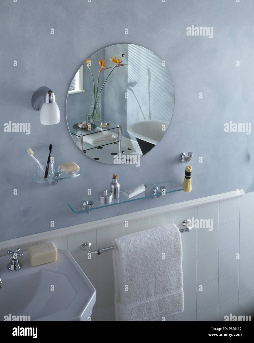 Circular unframed mirror and glass shelves above white towel on rail ...