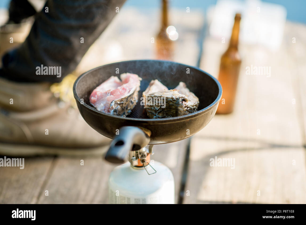 Frying two fish steakes on the burner during the picnic with beer and fishing tackles outdoors - Stock Image