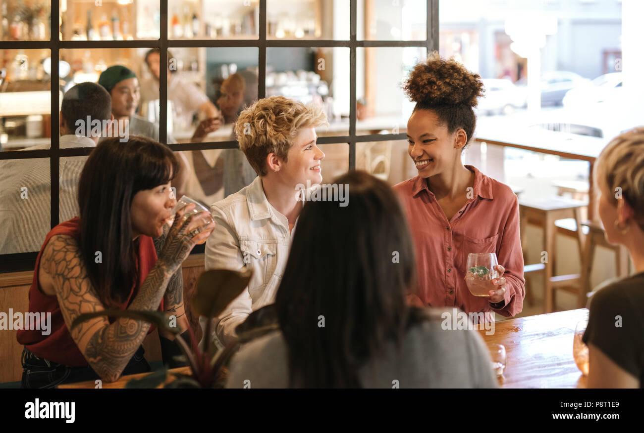 Young female friends laughing together over drinks in a bistro - Stock Image