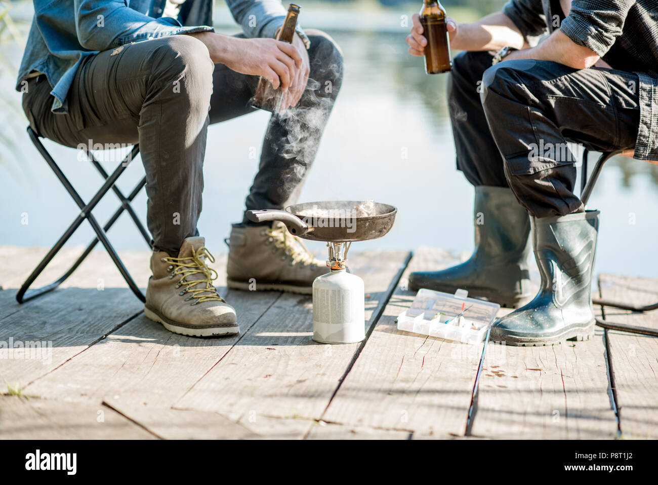 Two fishermen frying fish sitting with beer during the picnic on the wooden pier near the lake in the morning - Stock Image