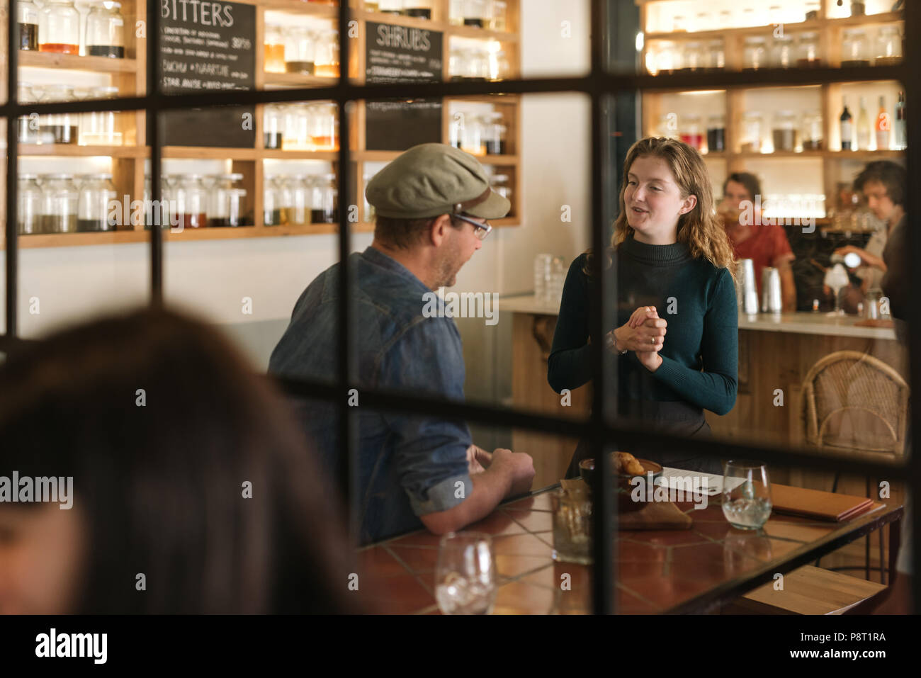 Smiling young waitress talking with a bistro customer - Stock Image