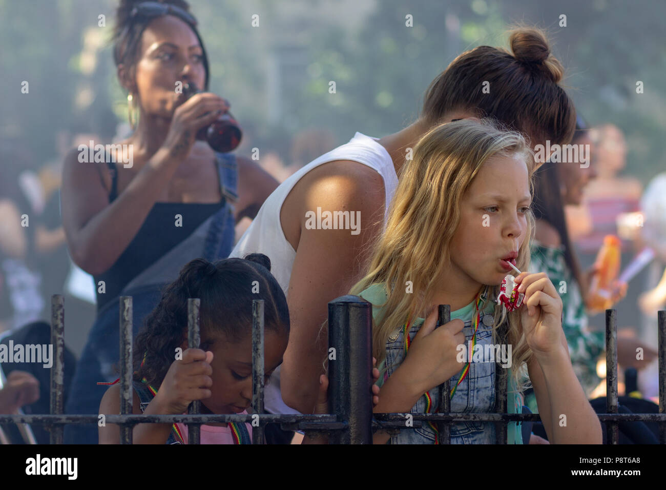 A woman and a girl indulging in quite different vices at St Paul's Carnival, Bristol - Stock Image