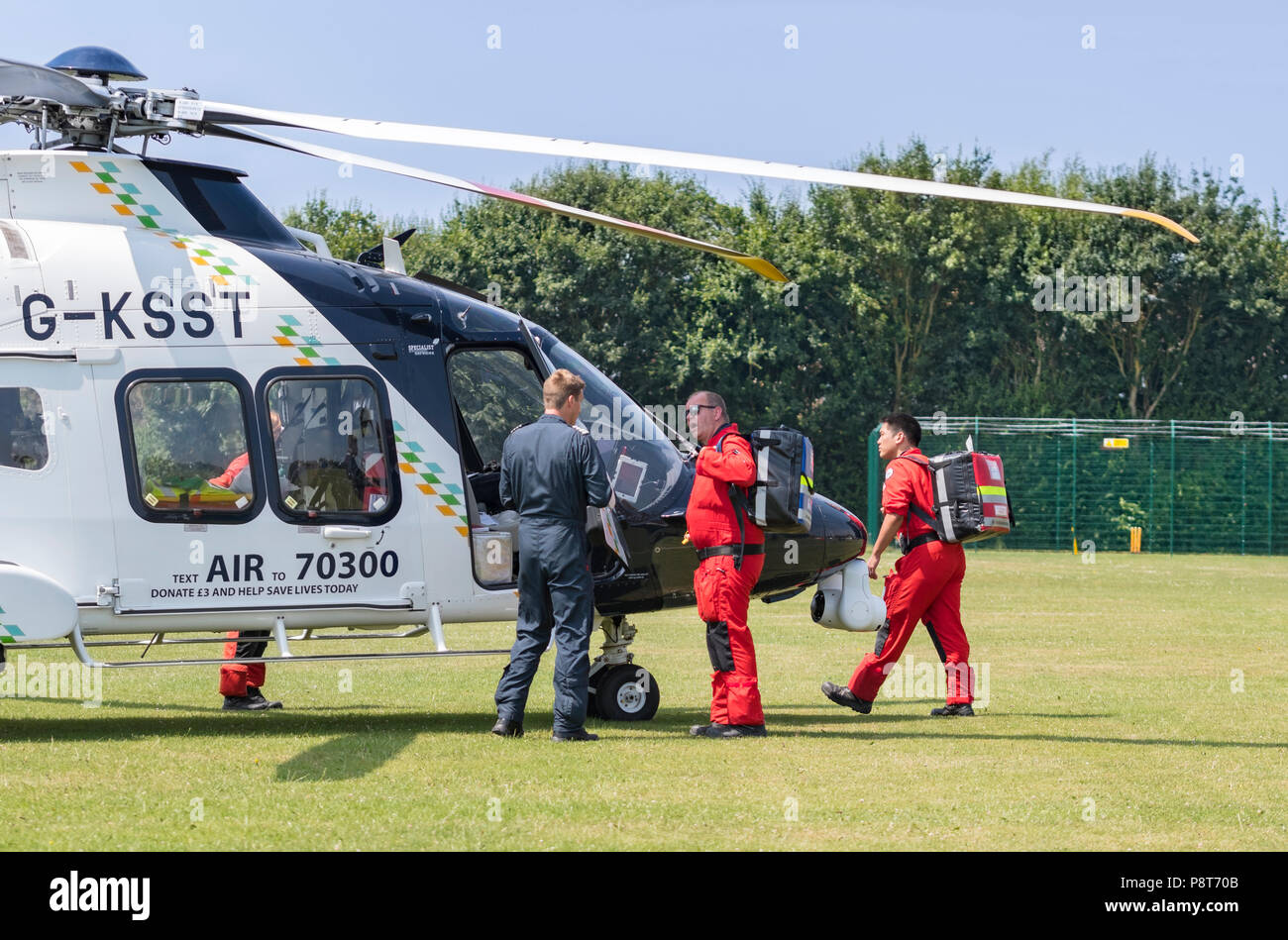 Paramedics and doctor of Kent, Surrey, Sussex Helimed air ambulance helicopter attending incident in England, UK. Aircraft is AgustaWestland AW169. - Stock Image