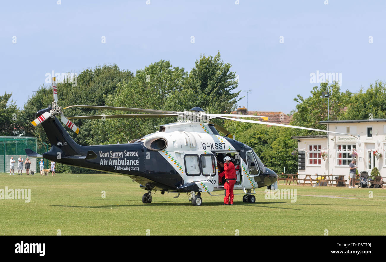 Pilot with helmet preparing to board a Helimed air ambulance helicopter (G-KSST) attending an accident in England, UK. AgustaWestland AW169. - Stock Image