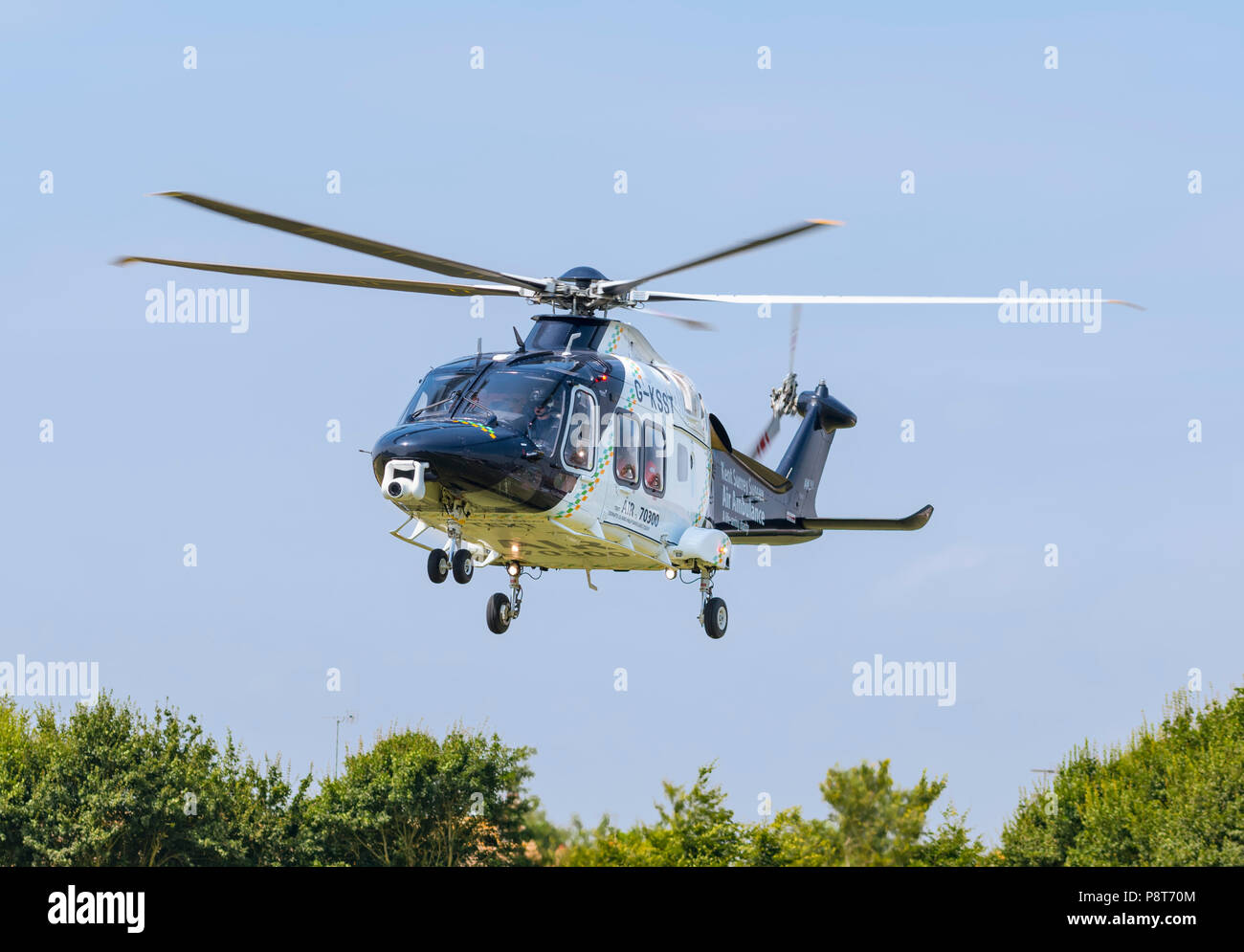 Kent, Surrey, Sussex air ambulance helicopter (G-KSST) taking off after attending accident in England, UK. Aircraft is AgustaWestland AW169. Medical. - Stock Image