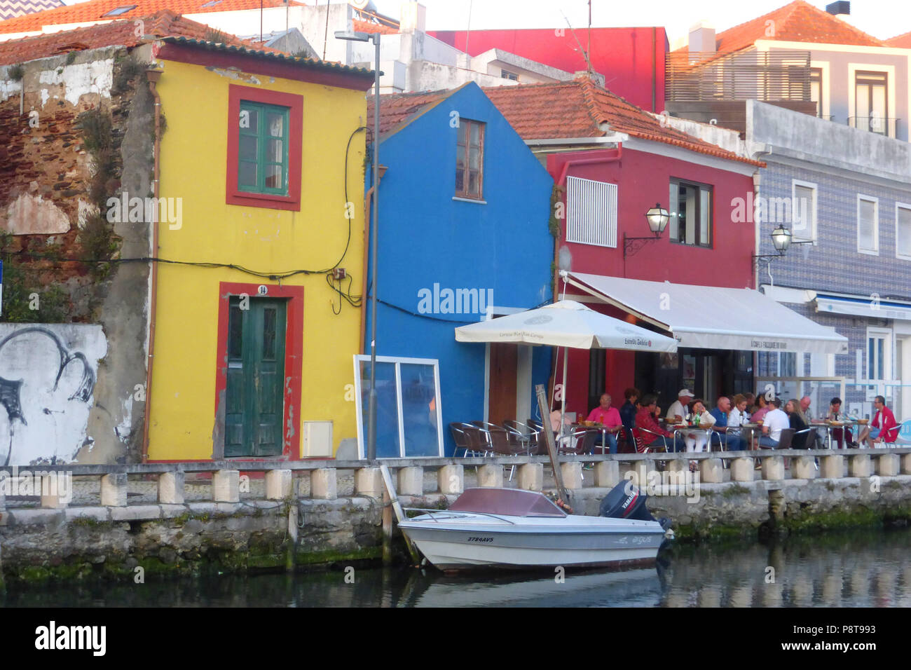 Canal waterfront and restaurant in front of old fishermen's houses at Aveiro, Portugal Stock Photo