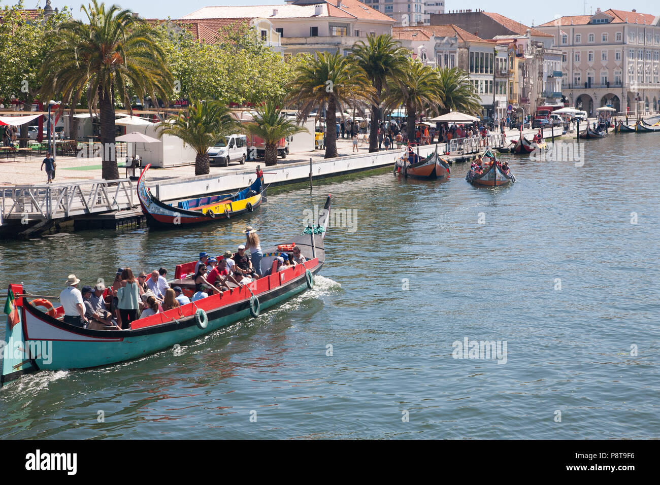 Canal in Aveiro, Portugal, busy with Moliceiros (boats formerly used to collect seaweed) ferrying sightseers. - Stock Image