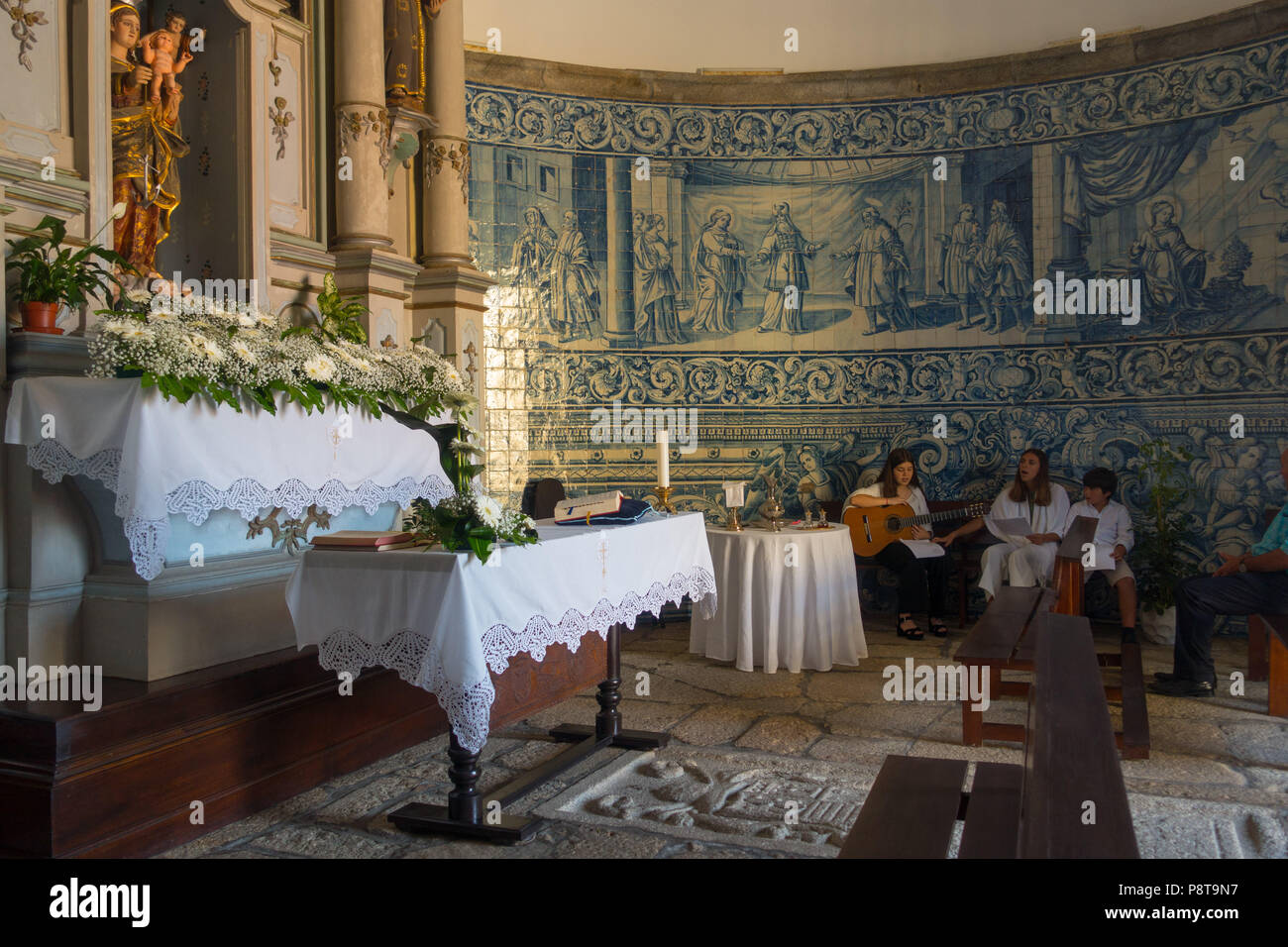 The round interior of Capela do Socorro, Vila do Conde, lined with blue azulejos depicting the life of Christ. Musicians welcoming a baptism party. Stock Photo
