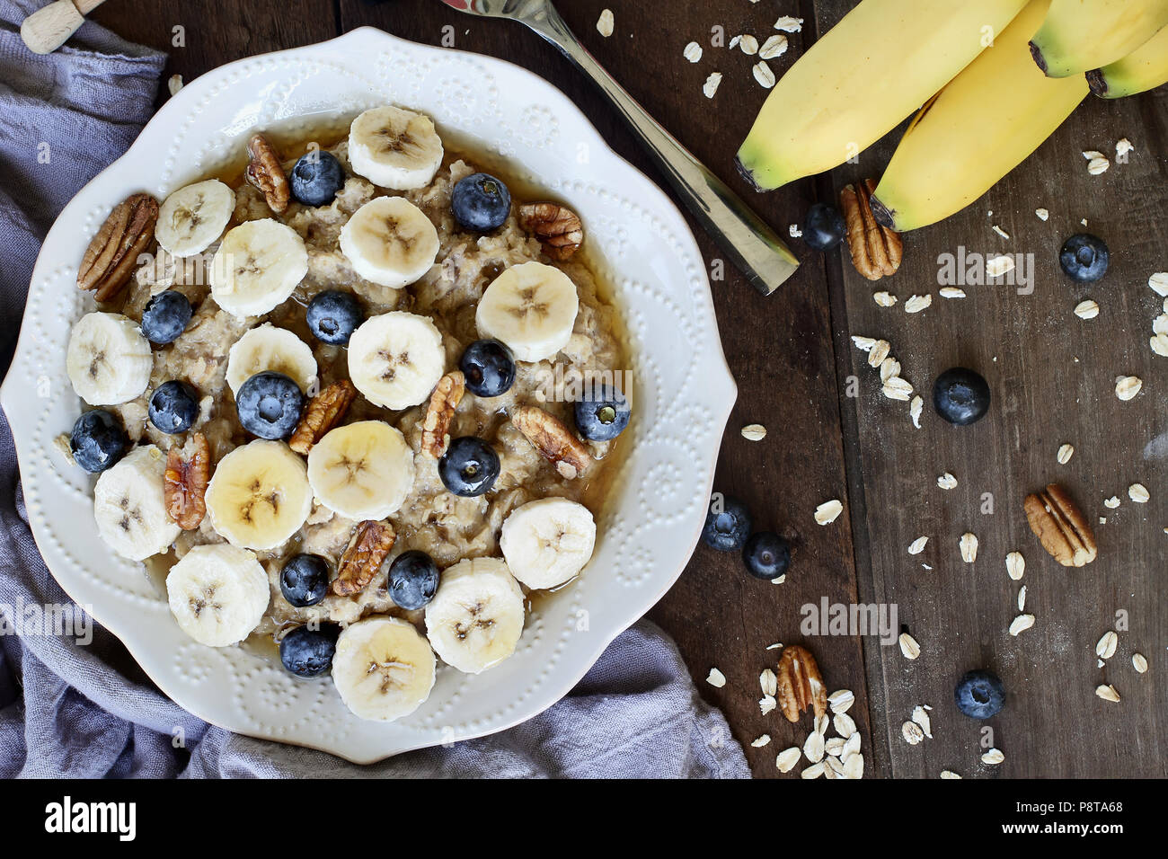 Hot breakfast of healthy oatmeal with pecans, bananas, blueberries and honey over a rustic background. Image shot from overhead. - Stock Image