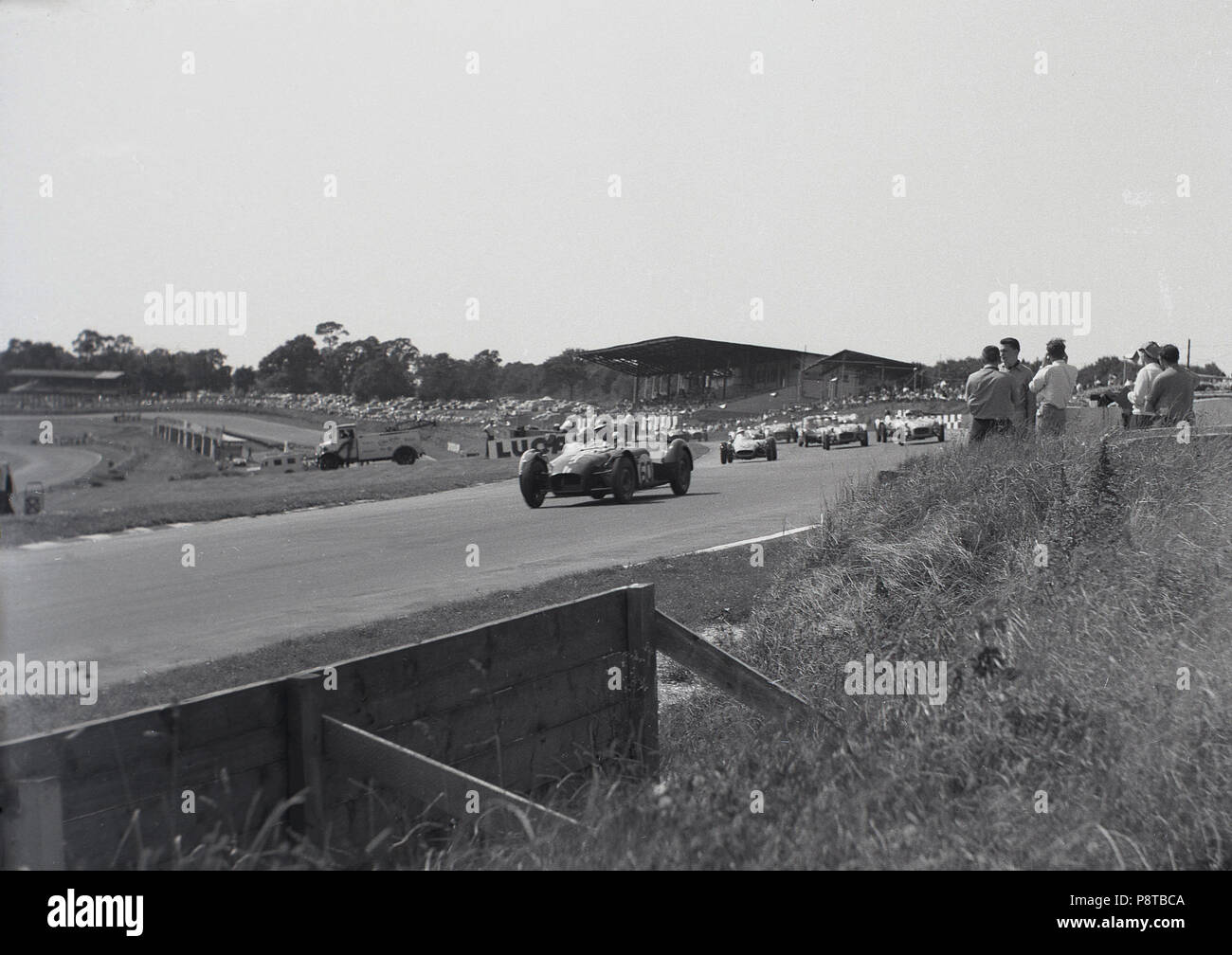 1950s, motor racing, single-seater open-wheel racing cars competing outside on a race track with spectators close to the action, England, UK. - Stock Image