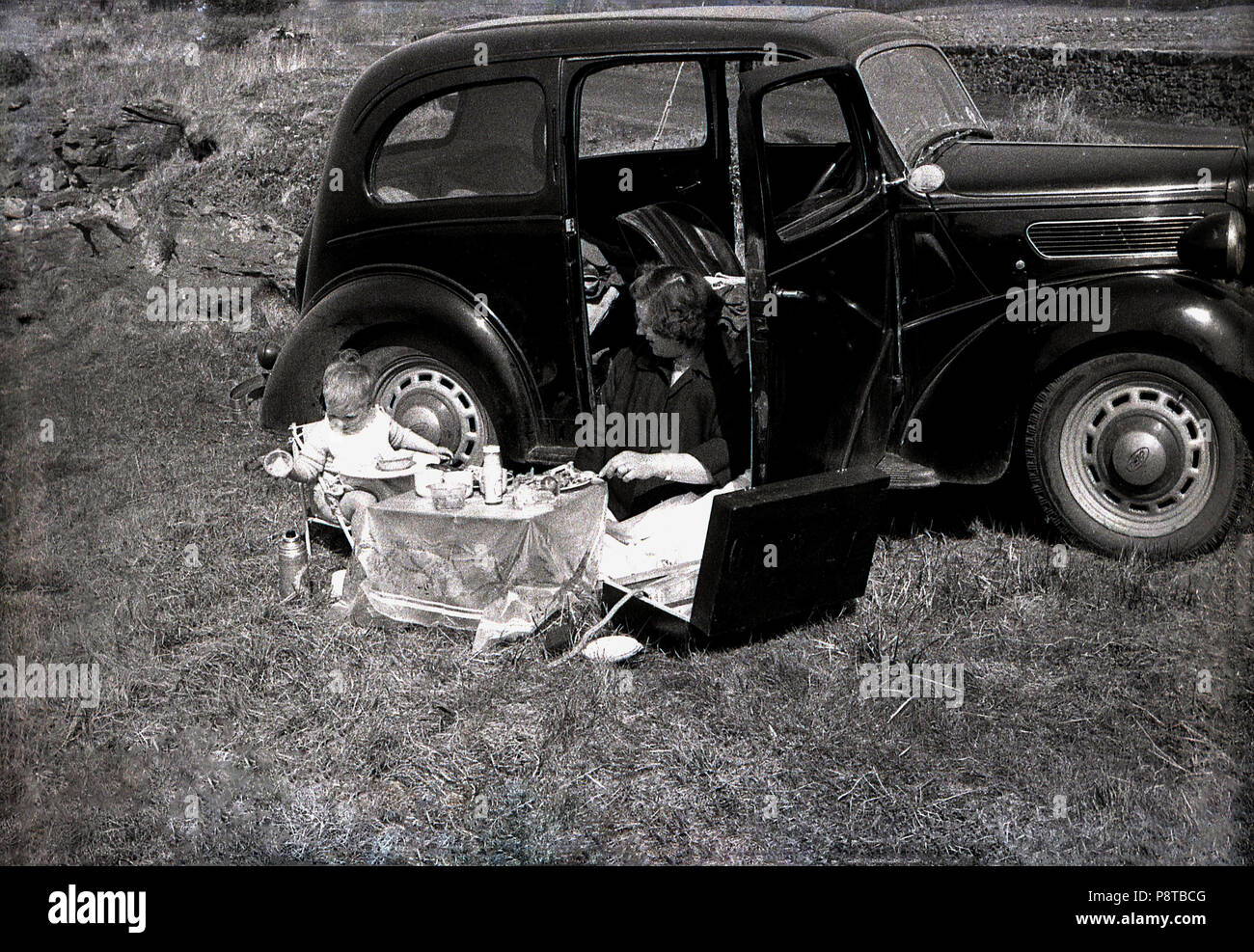 1950s, historical, a day out ....mother with young child sitting by their motor car having a civilised picnic set up on a small table with tablecloth, England, UK. - Stock Image