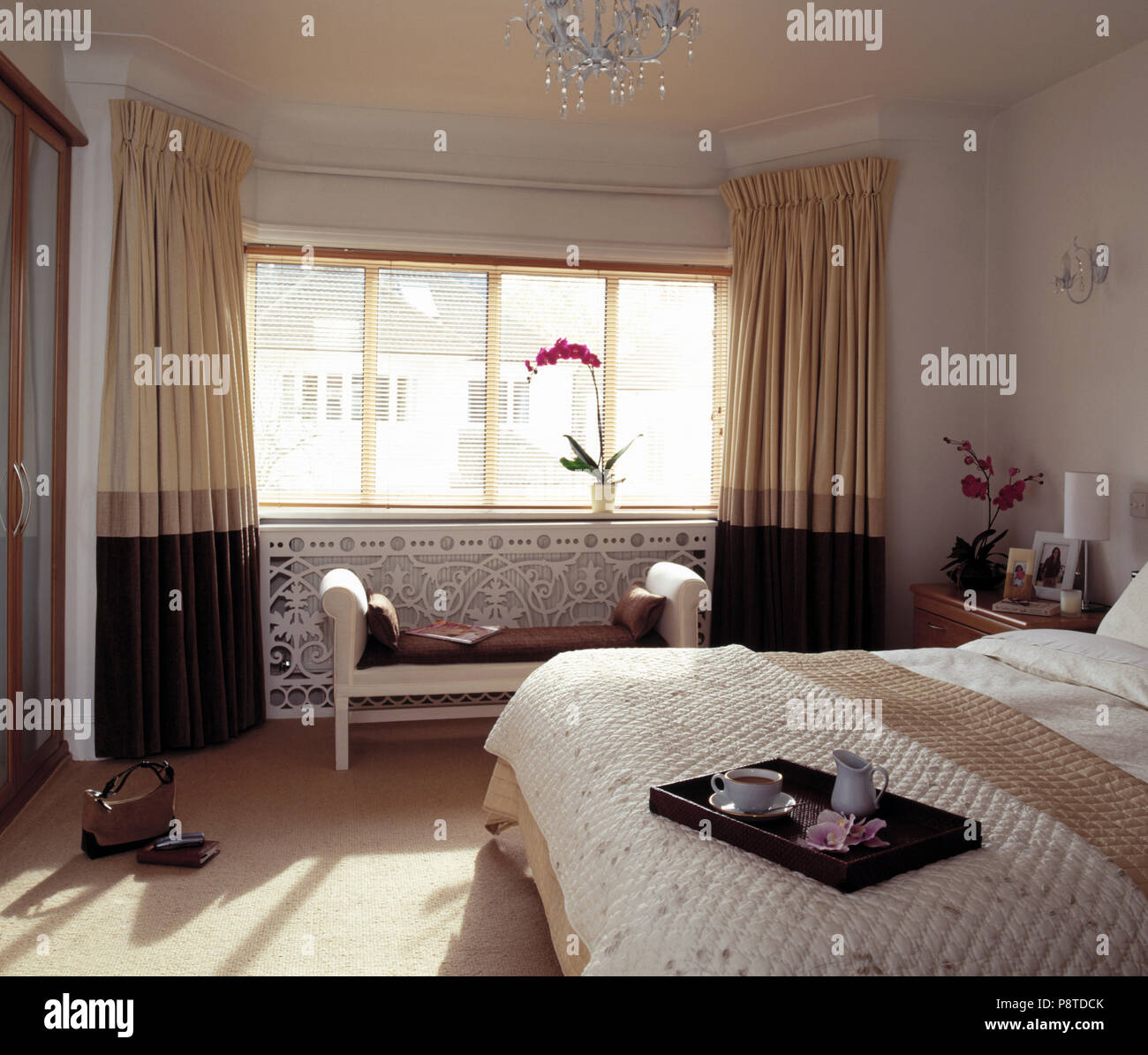 Large White Bedroom With A Built In Wardrobe Bay Window With Cream And Brown Curtains And Filigree Radiator Cover Stock Photo Alamy