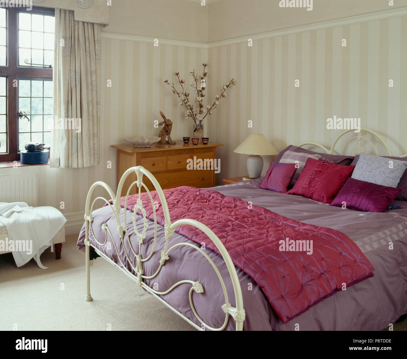 Bright pink silk cushions and throw on white iron bed with ...