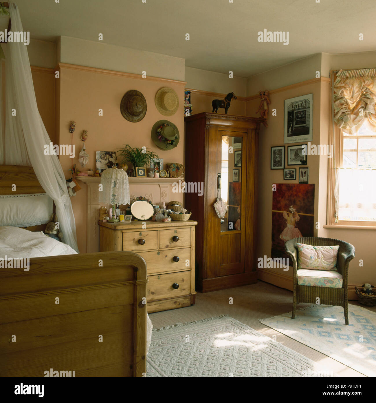 Pine chest of drawers and white voile drapes over wooden bed in ...