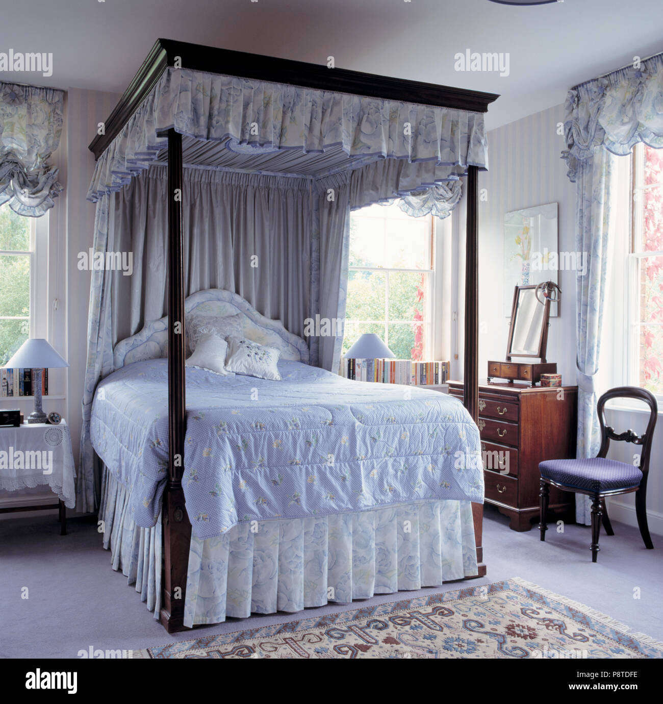 Blue White Drapes On Fourposter Bed With Blue Quilt In Traditional Country Bedroom Stock Photo Alamy