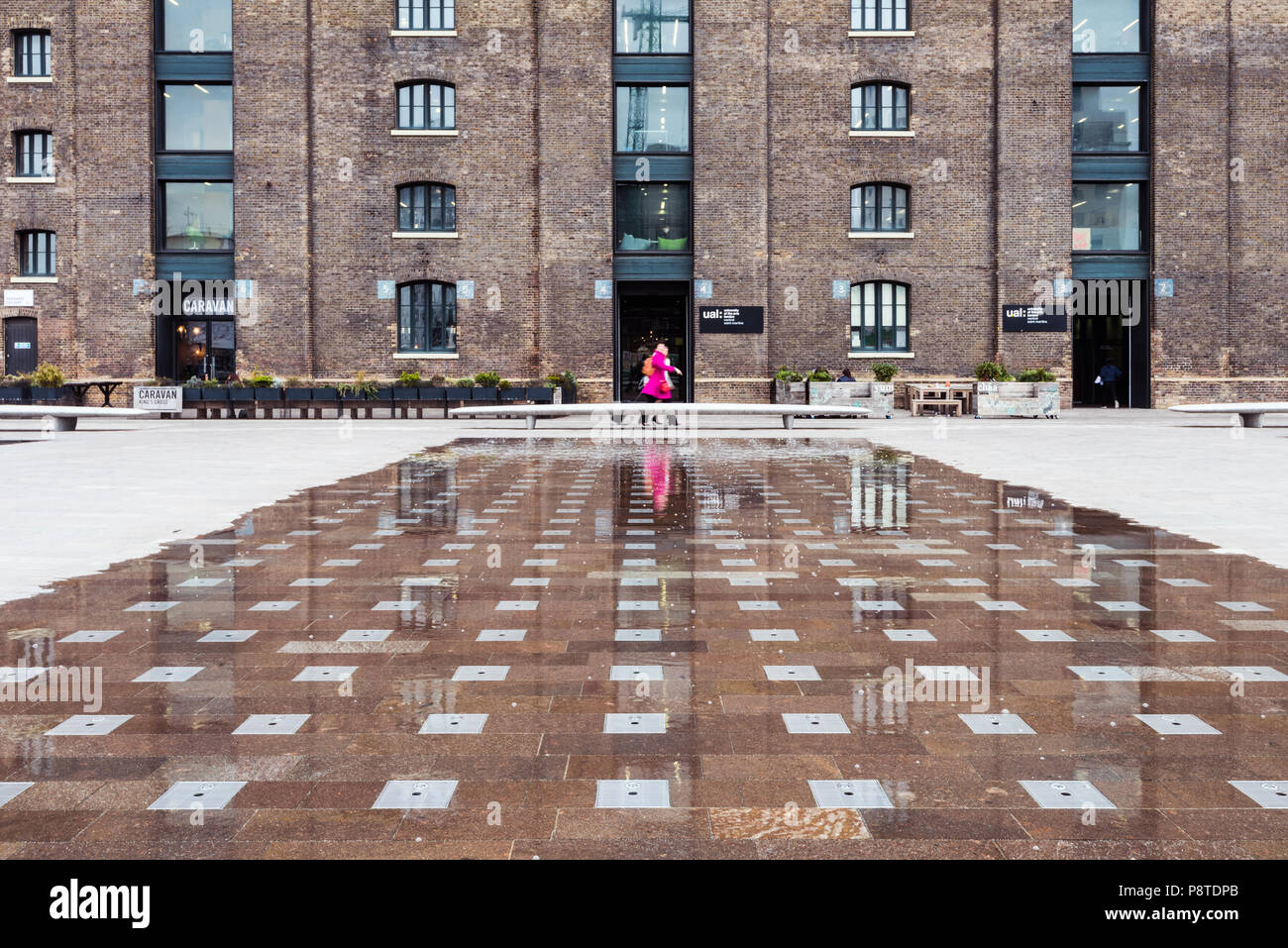 Low shooting angle of the University of the Arts London (UAL) in Granary Square, King's Cross, showing a woman in a pink coat positioned centrally - Stock Image