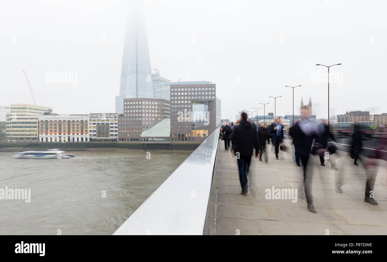 Monday morning commuters walking to work on London Bridge over the River Thames and towards the City and the Shard on a misty day - Stock Image