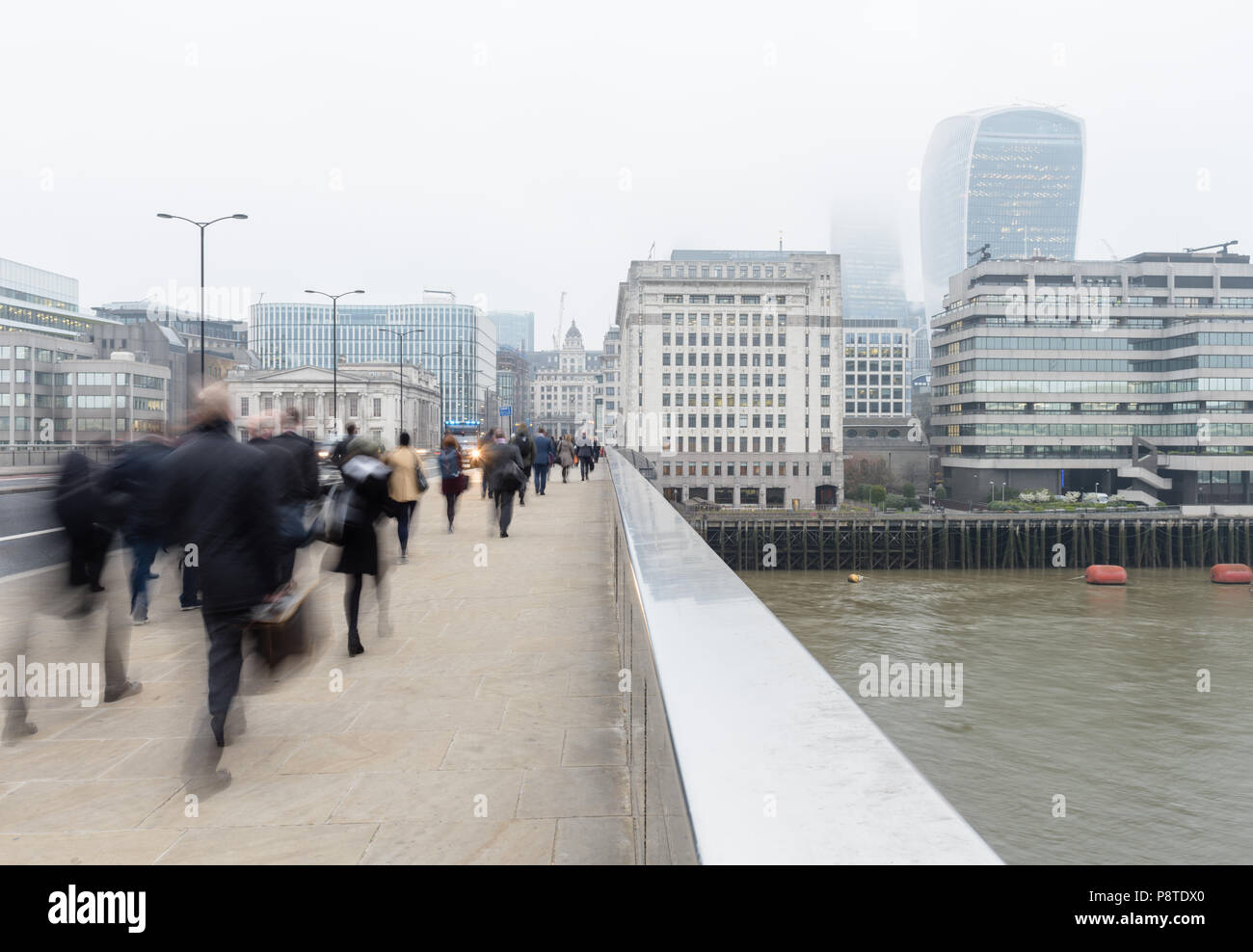Monday morning commuters walking to work on London Bridge over the River Thames and towards the City and Walkie Talkie building on a misty day - Stock Image
