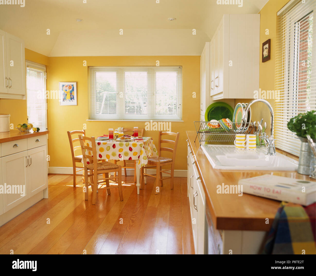 Wooden flooring in modern yellow kitchen with fitted white ...