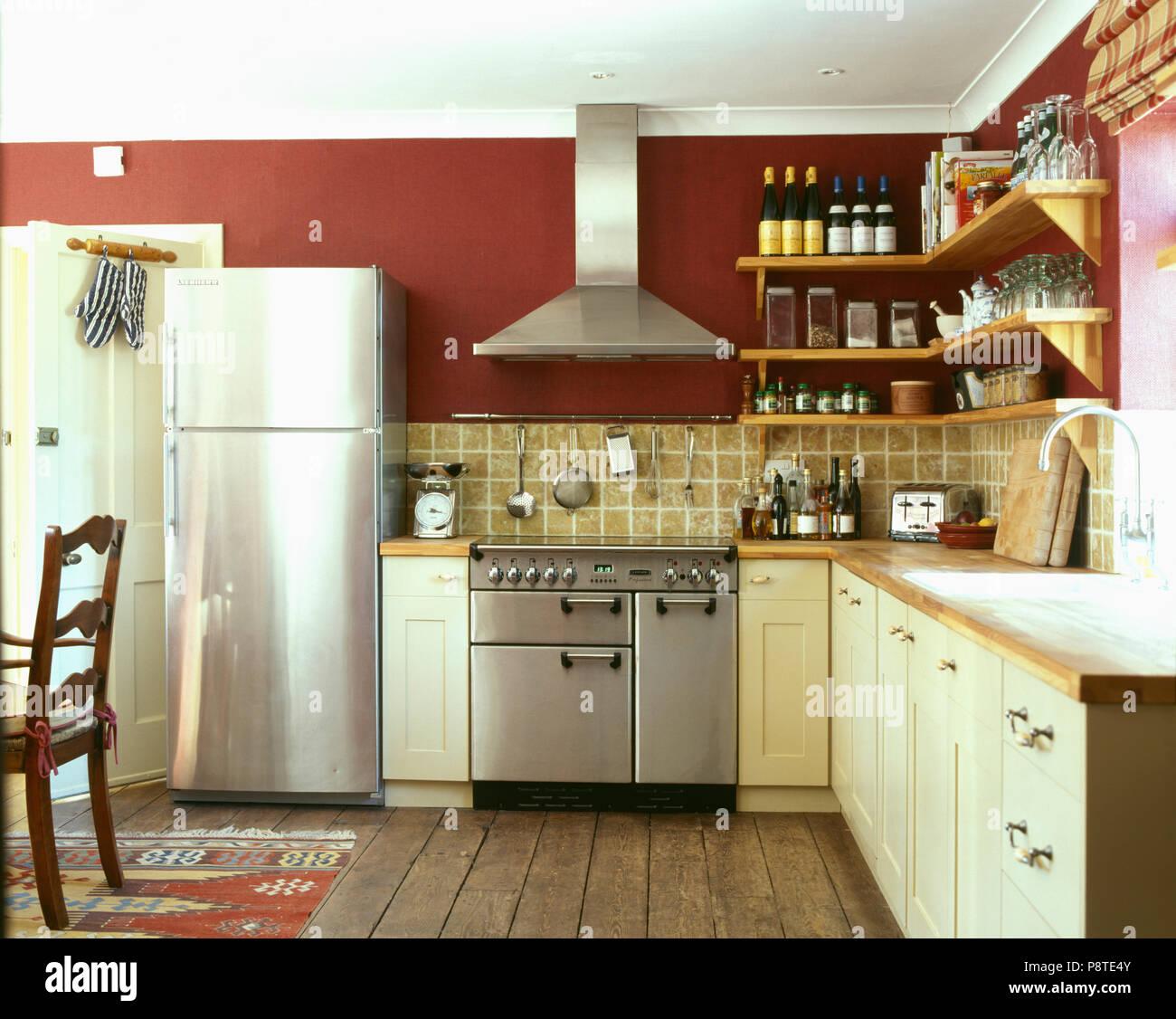 Stainless-steel fridge-freezer and range oven in modern red ...