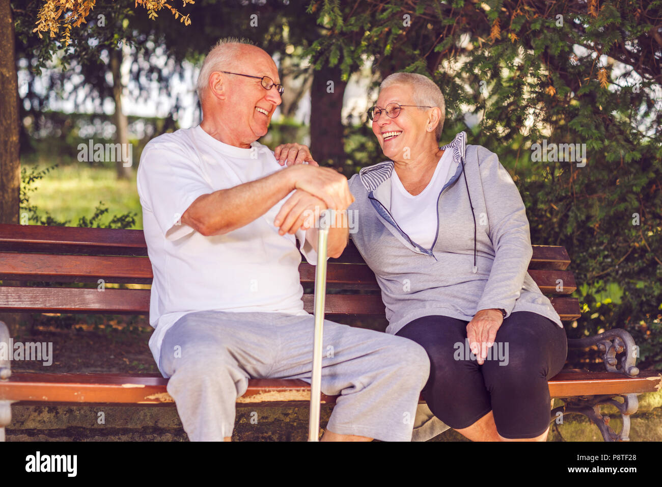 Smiling senior couple sitting together on a park bench - Stock Image