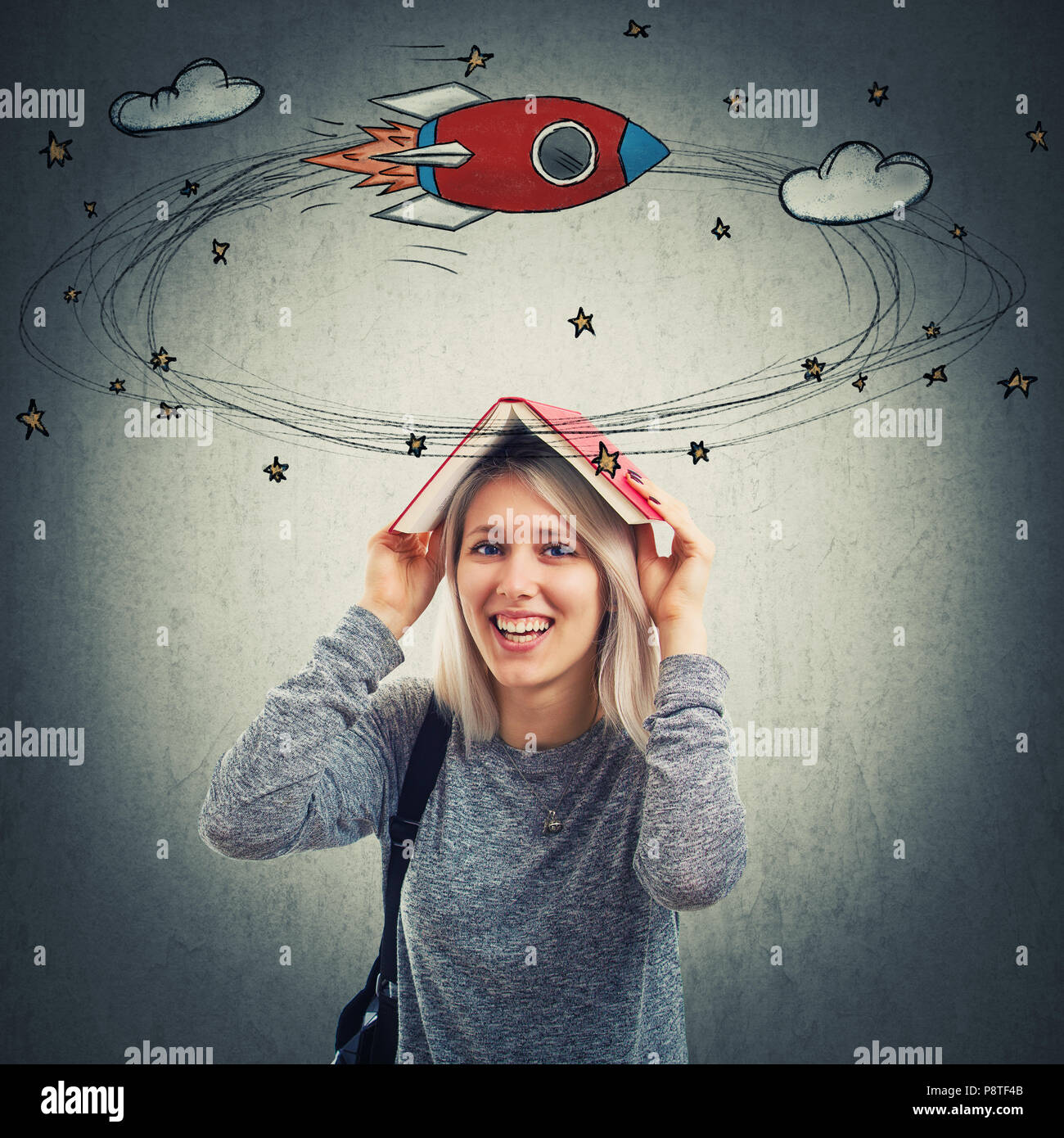 Smiling young woman holding a opened book over her head can't concentrate on learning. Dizzy disheveled girl going crazy with amount of study daydream - Stock Image