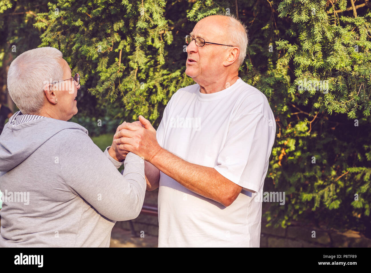 Happy family - Romantic senior couple enjoying walk in park together Stock Photo