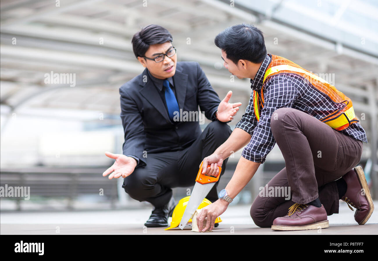 misunderstand teamwork between manager business man and young engineer discuss during project meeting at industrial construction site about the plan a - Stock Image
