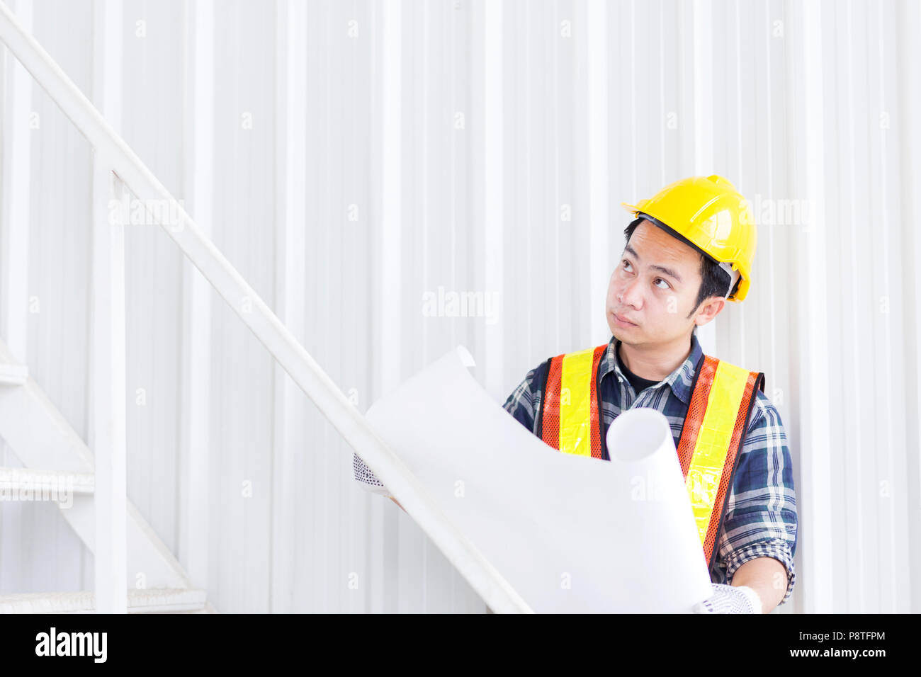 Smart civil engineer wear safety helmet and hold construction and smart civil engineer wear safety helmet and hold construction and architect blueprint project in hand and check the design of work at office site in b malvernweather Image collections