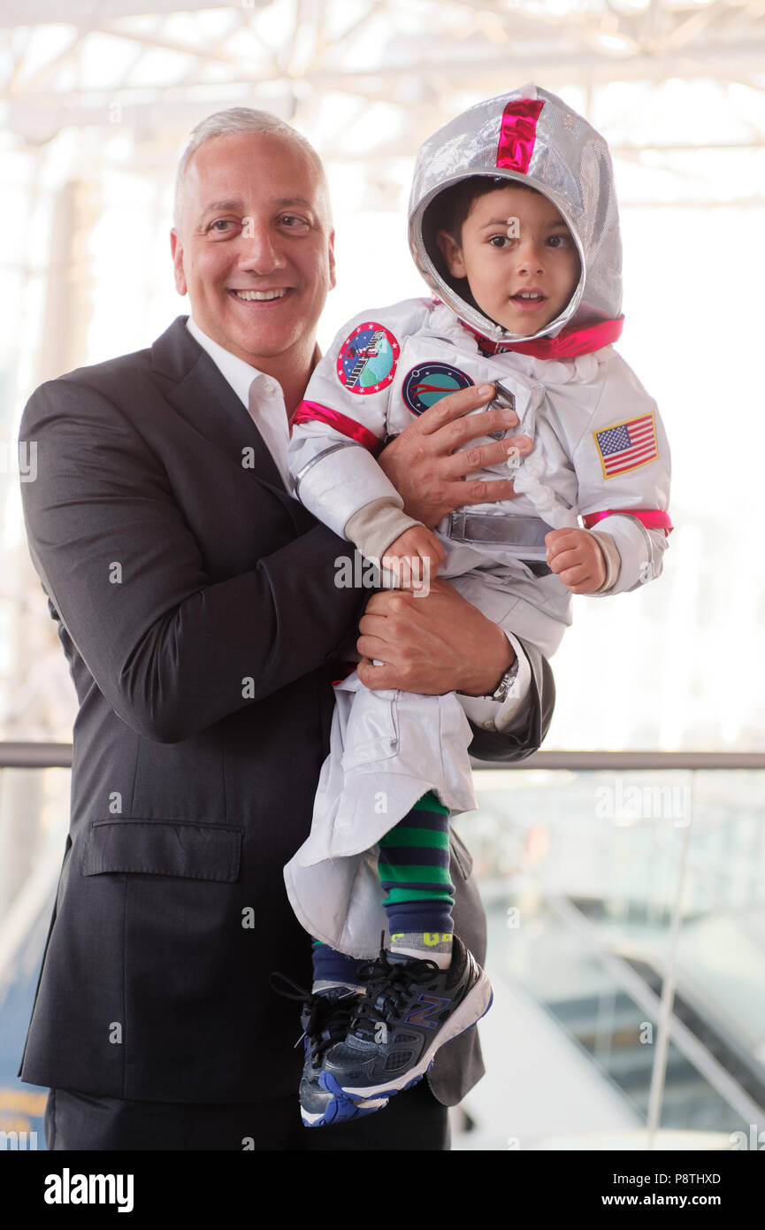 Garden City, New York, USA. June 21, 2018. NASA space shuttle astronaut MIKE MASSIMINO poses holding GIOVANNI, a 3 1/2 year old boy wearing a spacesuit costume, from Manhasset, before the former astronaut gave a lecture at the Cradle of Aviation Museum. - Stock Image