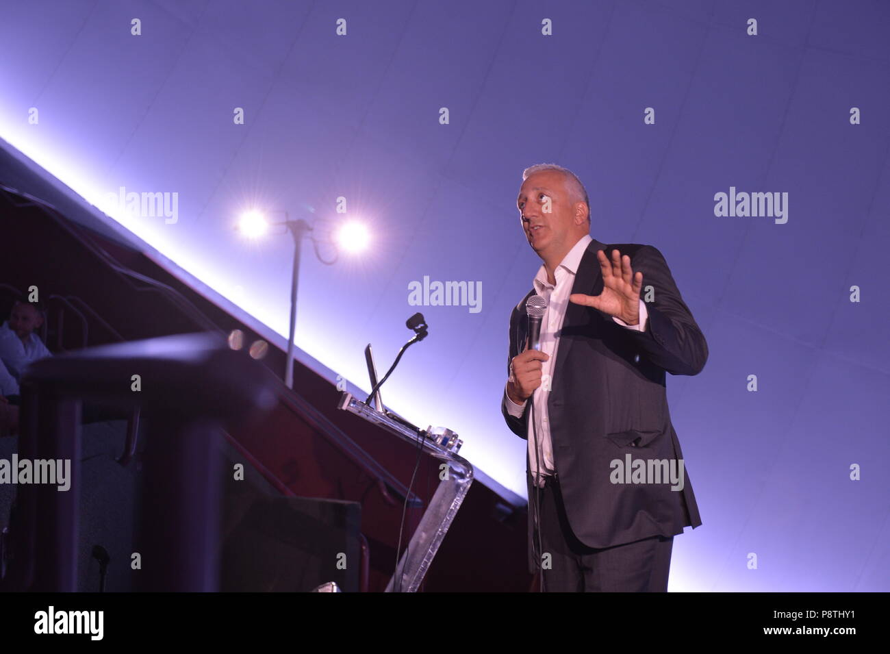 Garden City, New York, USA. June 21, 2018. Former NASA space shuttle astronaut MIKE MASSIMINO, a Long Island native, gestures as he stands at podium on stage during his free lecture in the JetBlue Sky Theater Planetarium at the Cradle of Aviation Museum. Stock Photo