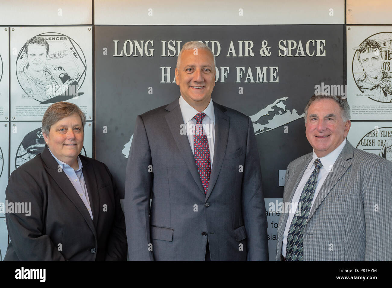 Garden City, New York, USA. June 21, 2018. L-R, DEBORAH HENLEY, VP Executive Editor of Newsday, representing inductee aviator and Newsday founder Alicia Patterson; Inductee former NASA astronaut MIKE MASSIMINO; and LOUIS MANCUSO JR, representing his parents, inductees Louis and Carol Mancuso, pose at Long Island Air & Space Hall of Fame Wall at Cradle of Aviation Museum during Class of 2018 Induction. - Stock Image