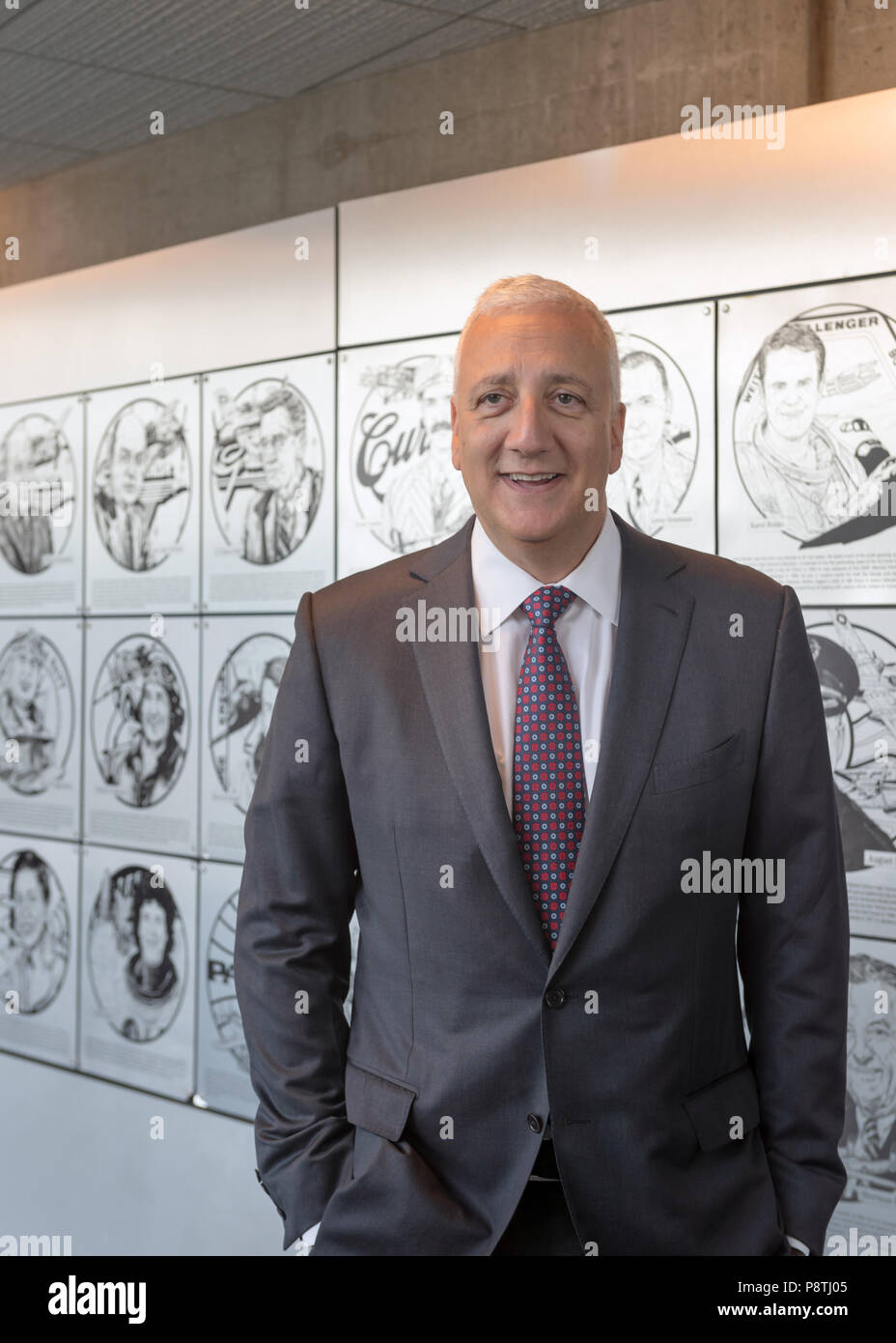 Garden City, New York, USA. June 21, 2018. Former NASA space shuttle astronaut MIKE MASSIMINO stands next to Long Island Air & Space Hall of Fame wall of plaques, during his induction into Class of 2018 at Cradle of Aviation Museum. - Stock Image