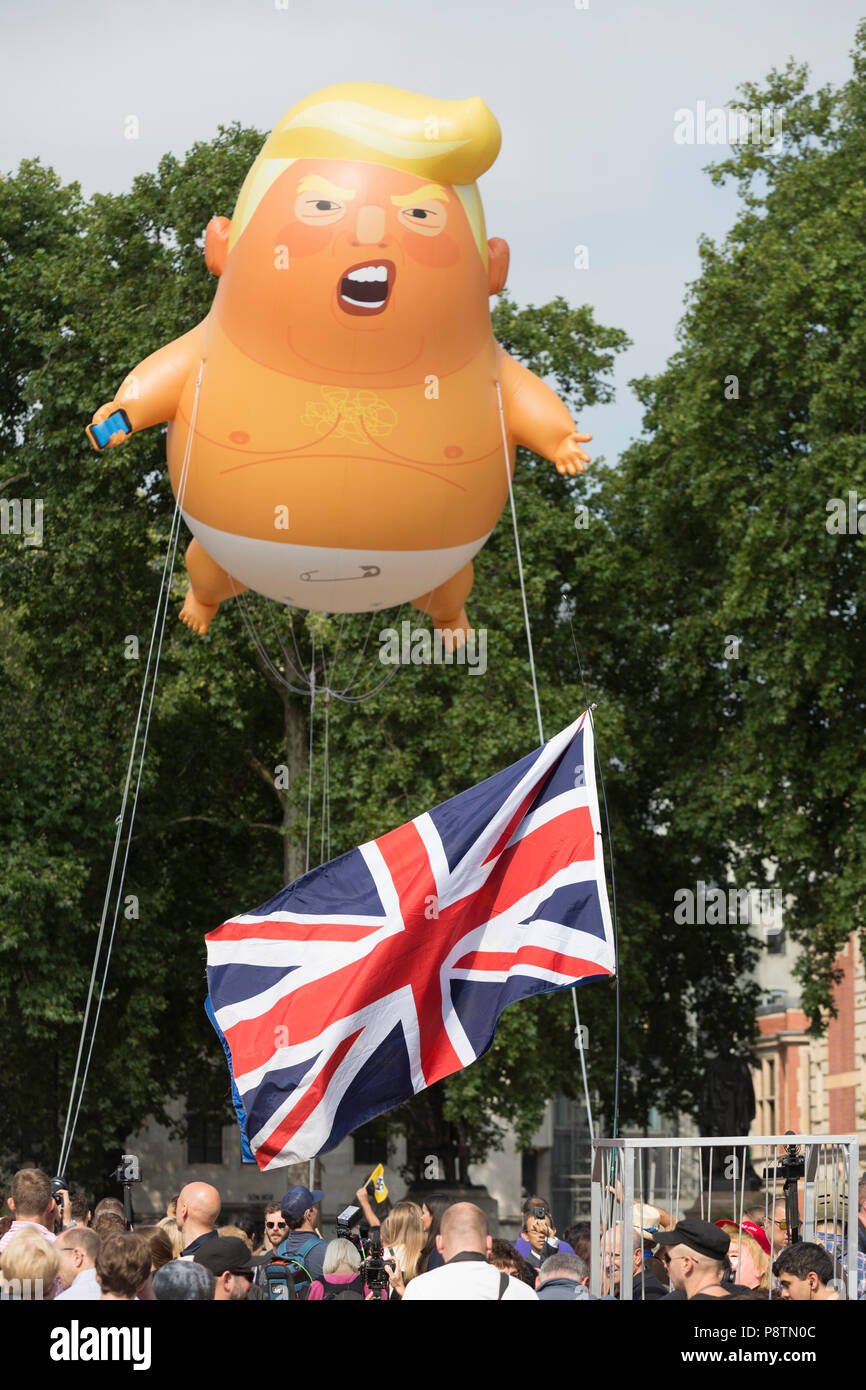 London, UK. 13th July, 2018. The inflatable balloon called Baby Trump flies above Parliament Square in Westminster, the seat of the UK Parliament, during the US President's visit to the UK. Baby Trump is a 20ft high orange blimp depicting the US President as an enraged, smartphone-clutching infant - and given special permission to appear above the capital by London Mayor Sadiq Khan because of its protest rather than artistic nature. It is the brainchild of Graphic designer Matt Bonner. Credit: RichardBaker/Alamy Live News Stock Photo