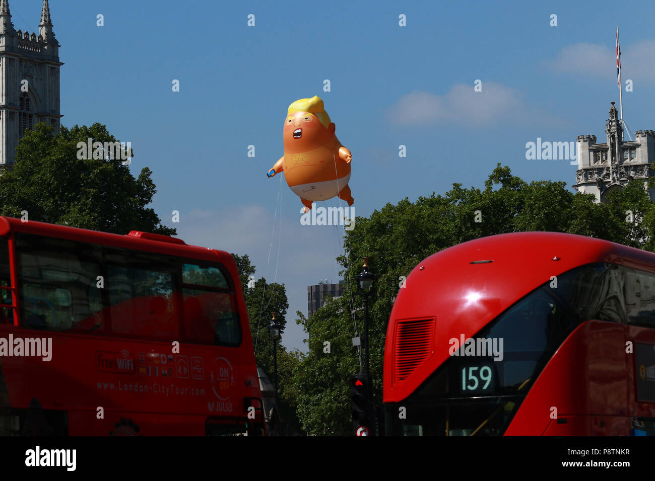 London, UK. 13th July, 2018. A Donald Trump baby blimp, mocking the American President, is flown above Westminster Square in London, as the President of the United States of America visits London, and has meetings with Prime Minister Theresa May and HM Queen Elizabeth II. Donald Trump baby blimp protest, London, on July 13, 2018. Credit: Paul Marriott/Alamy Live News Stock Photo