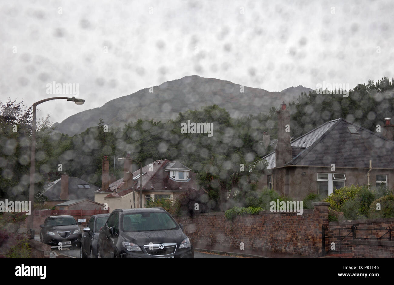 13 July 2018 UK Weather. Forecast predicted 95% chance of rain for Edinburgh, Scotland heavy shower arrived around 3pm in the afternoon, much needed after a few very dry weeks. View towards the summit of Arthur Seat. - Stock Image