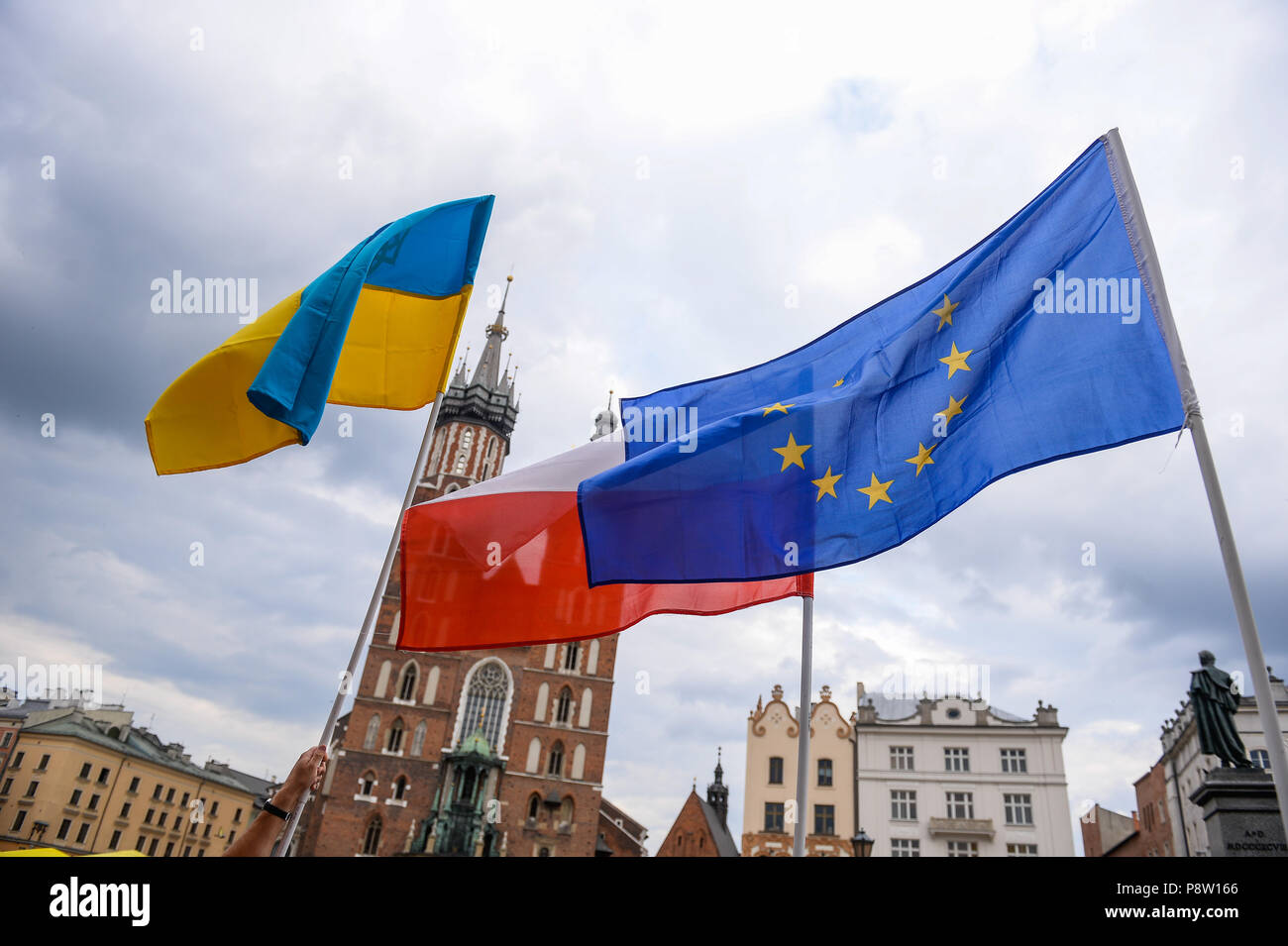 Ukrainian, Polish and European Union flags are seen during the protest. Protest demanding the release of the Ukrainian filmmaker and writer, Oleg Sentsov at the Main Square in Krakow who was sentenced to 20 years for conspiracy to commit terror acts. - Stock Image